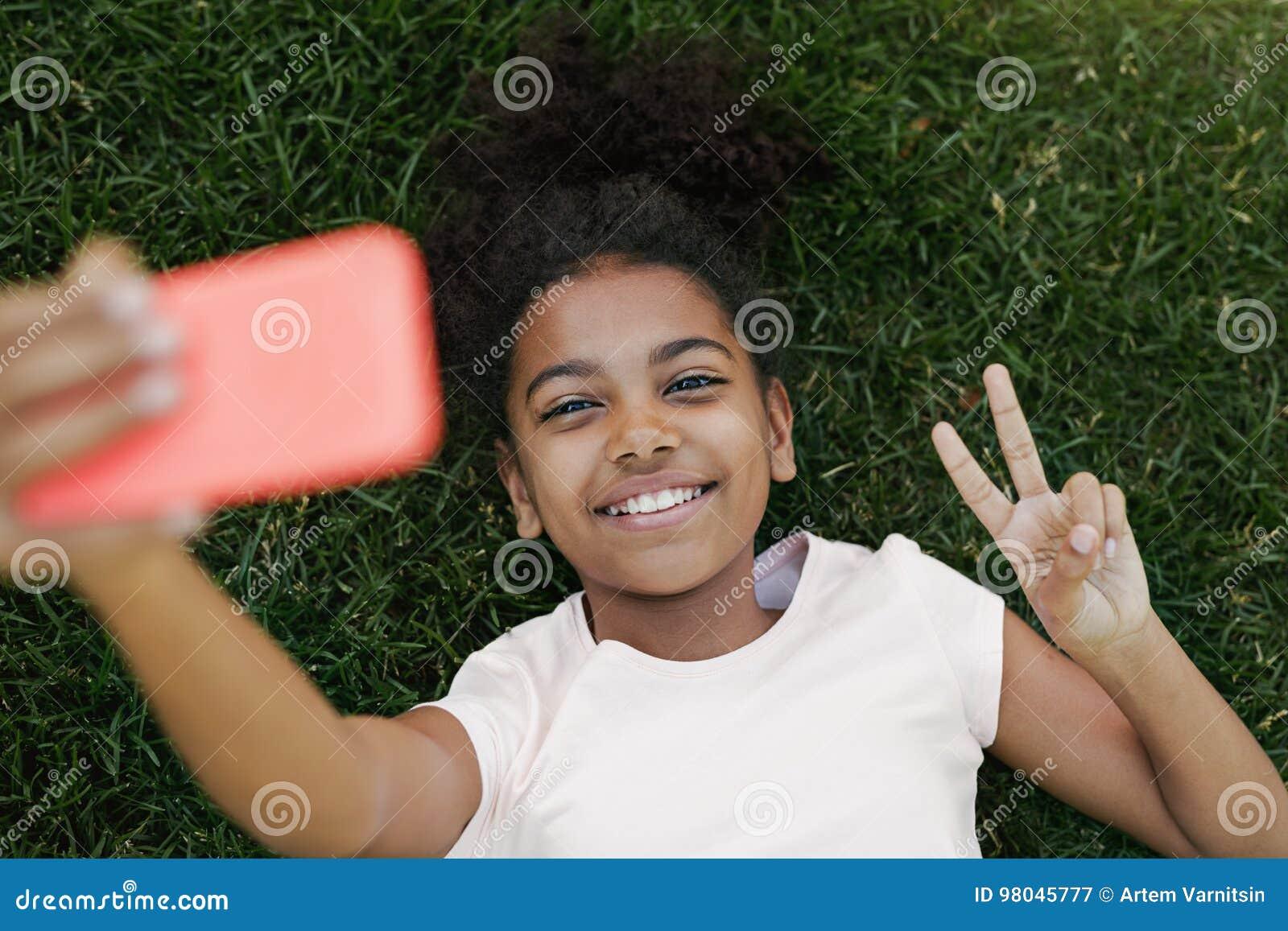 Uśmiechnięta dziewczyna bierze selfie na jej smartphone