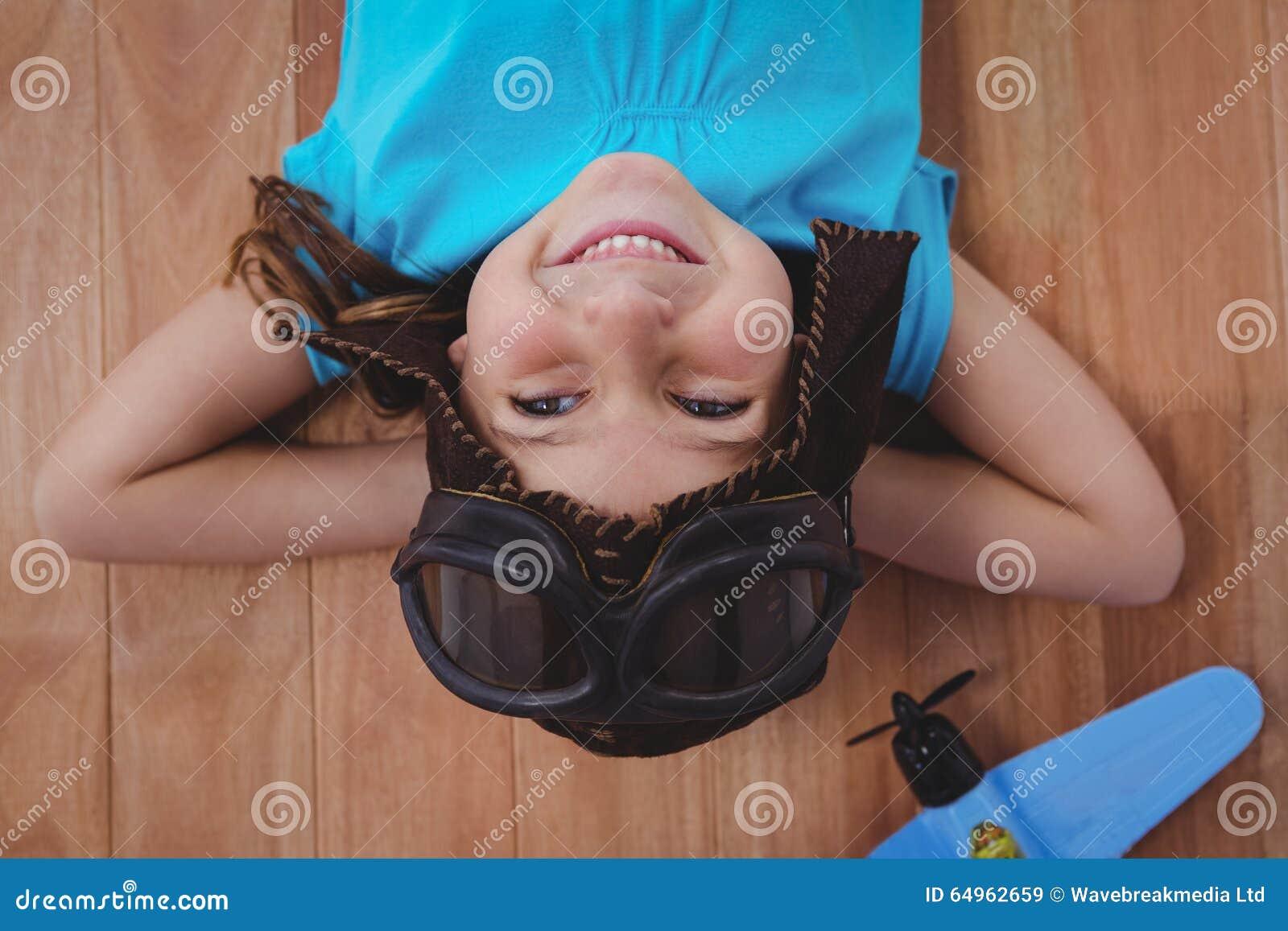 Uśmiechnięta dziewczyna kłaść na podłogowym jest ubranym lotnika kapeluszu i szkłach