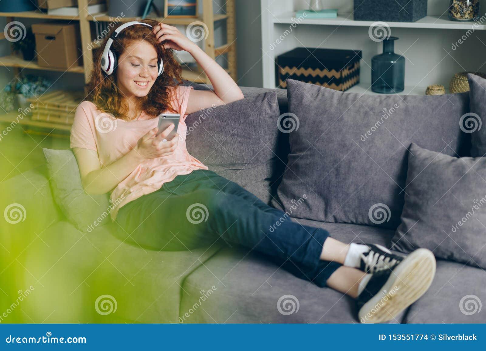 Uśmiechnięta dziewczyna słucha muzyka przez hełmofonów używać smartphone w domu