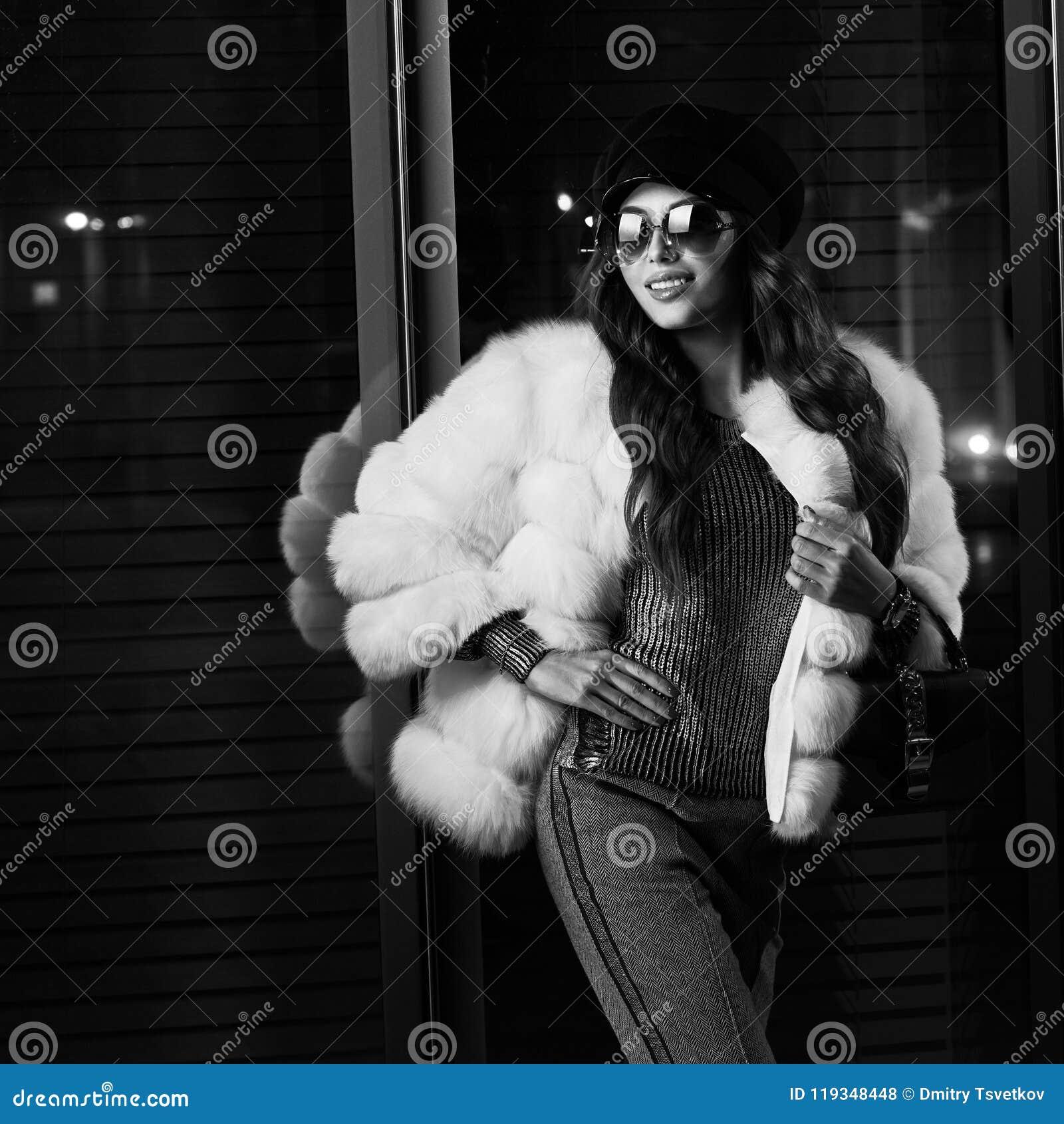 Uśmiechnięta dziewczyna w modnym białym futerkowym żakiecie i okularach przeciwsłonecznych