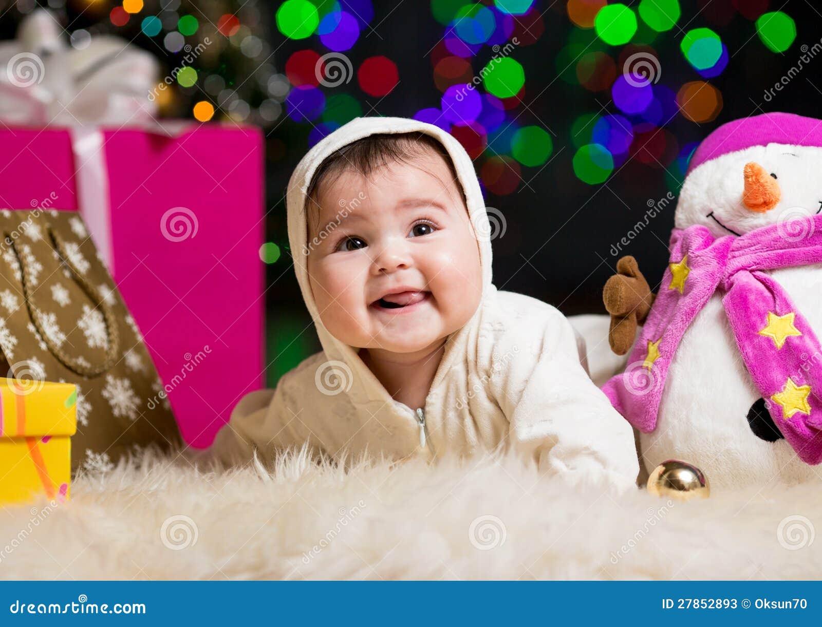 Uśmiechnięta dziewczynka blisko Choinki z prezentami