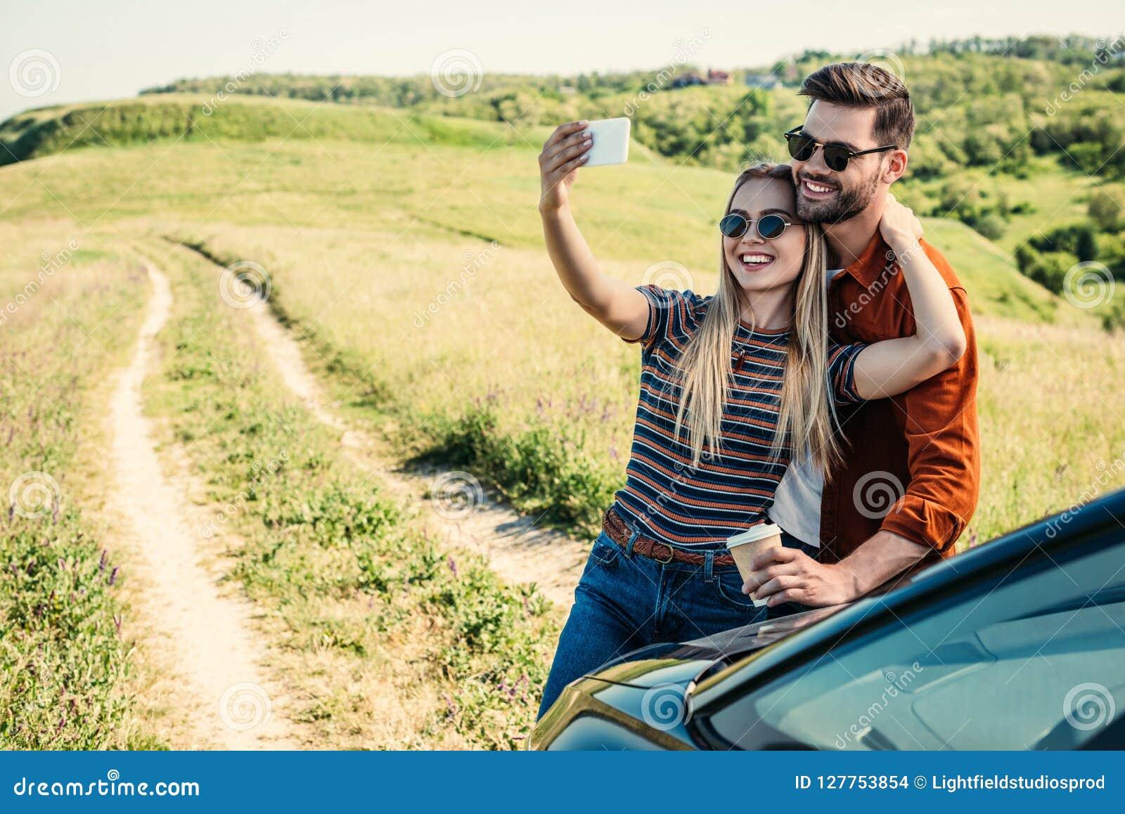 Uśmiechnięta elegancka para w okularach przeciwsłonecznych z filiżanką bierze selfie na smartphone blisko samochodu na wiejskim