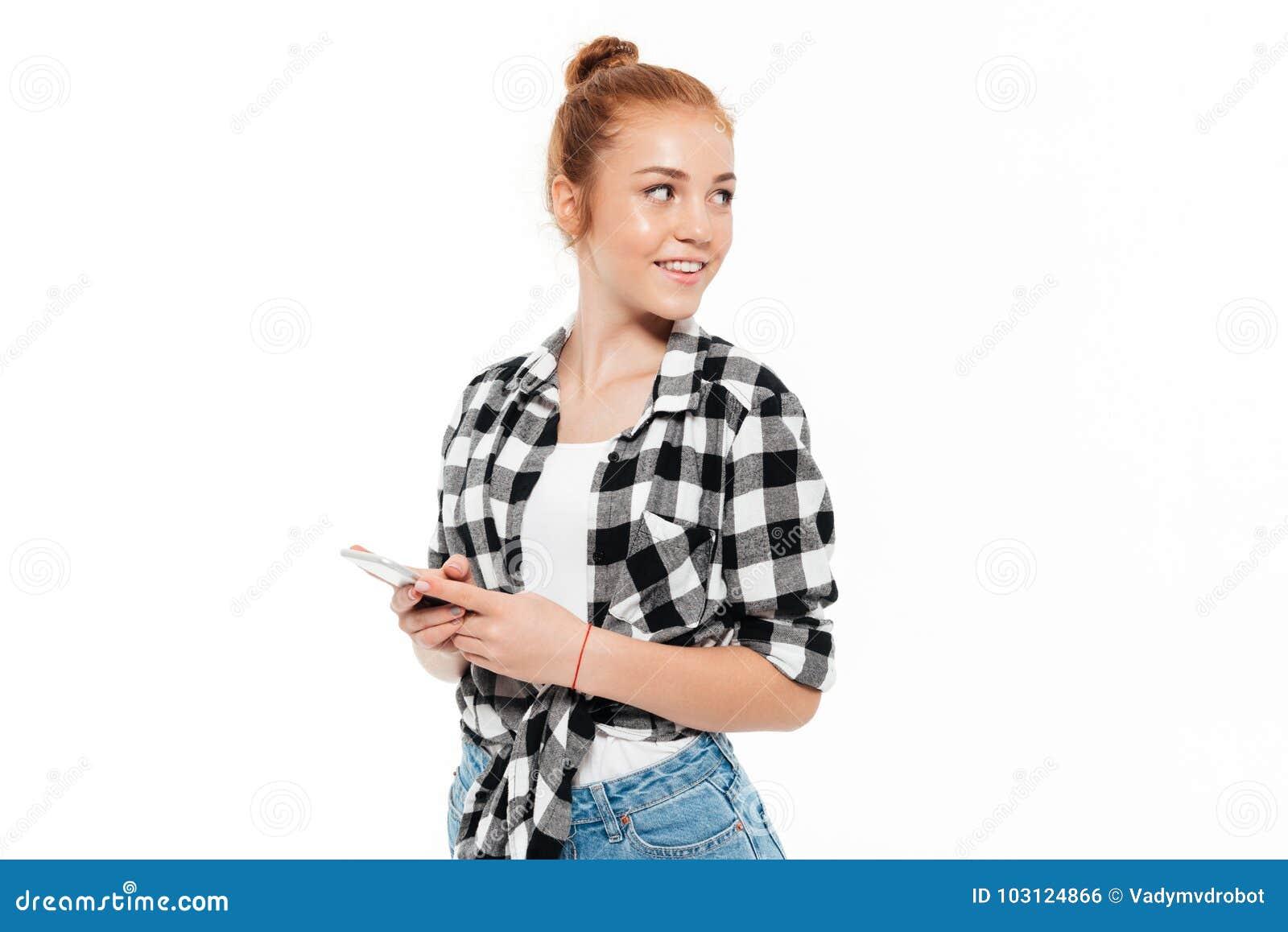 Uśmiechnięta imbirowa kobieta trzyma smartphone w koszula i cajgach