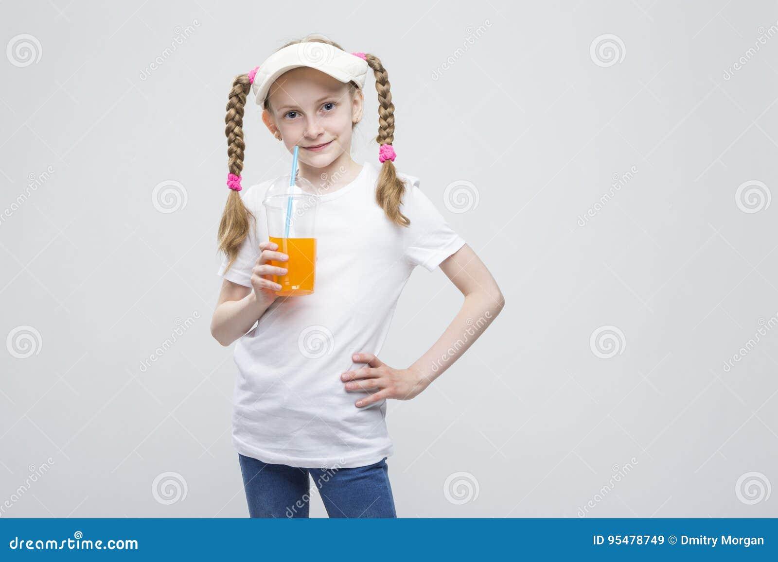 Uśmiechnięta Kaukaska Blond dziewczyna Trzyma filiżankę sok przeciw bielowi w naliczku