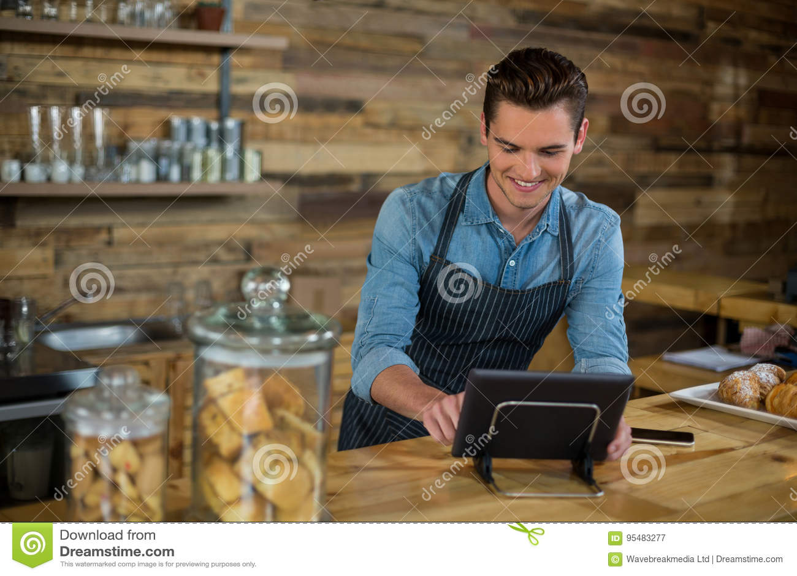 Uśmiechnięta kelner pozycja przy kontuarem używać cyfrową pastylkę