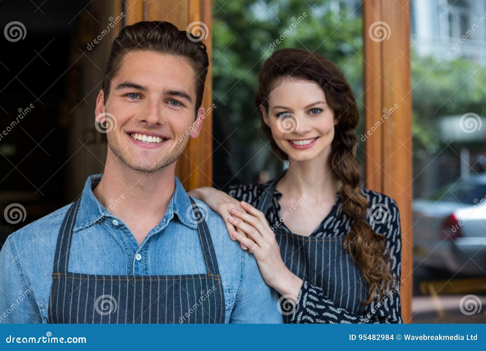 Uśmiechnięta kelnera i kelnerki pozycja na zewnątrz kawiarni
