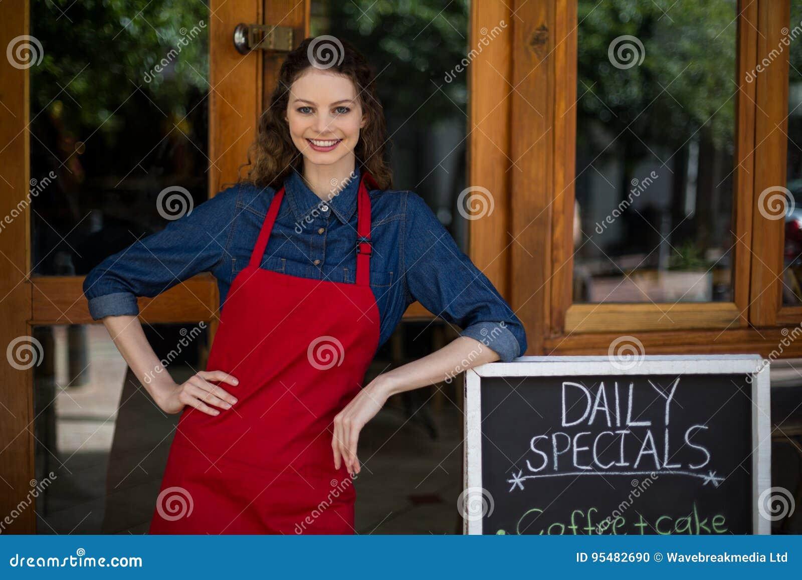 Uśmiechnięta kelnerka opiera na menu desce na zewnątrz kawiarni