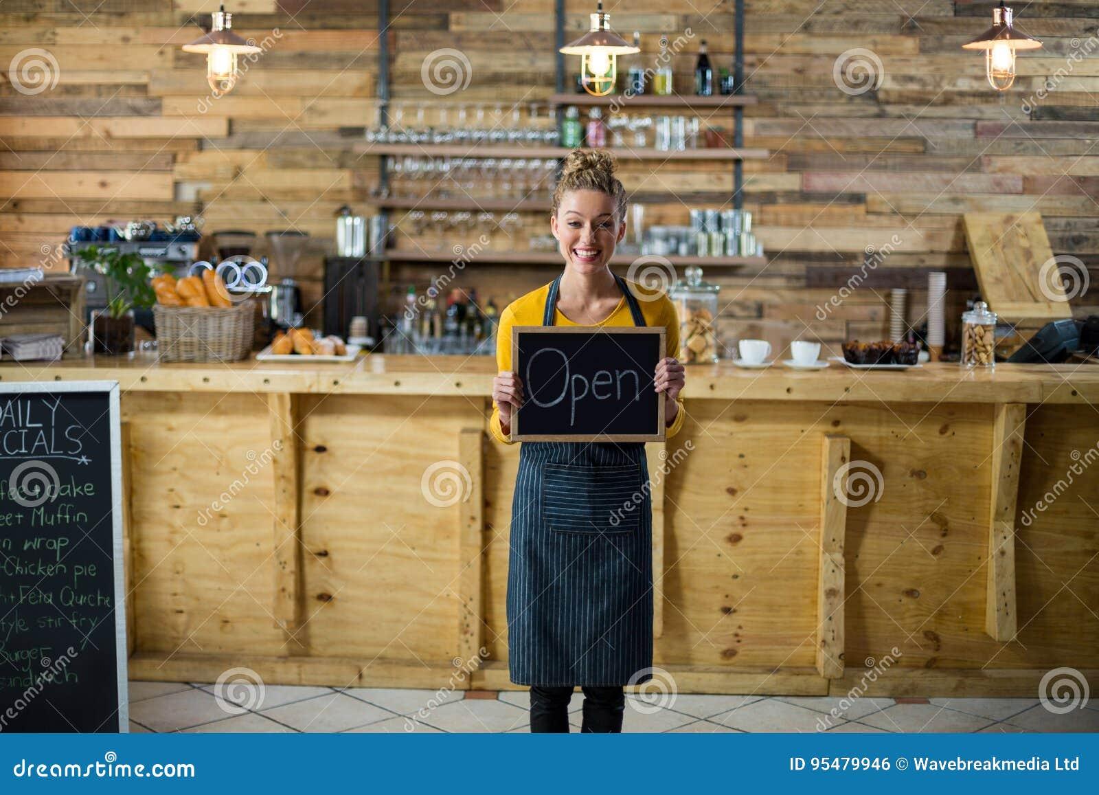 Uśmiechnięta kelnerki pozycja z otwartą znak deską w kawiarni