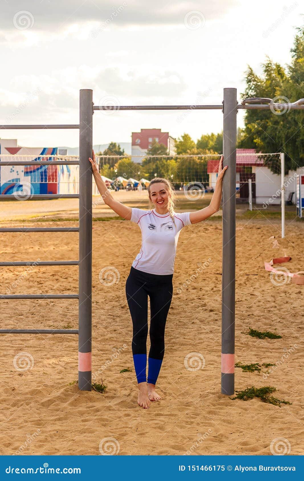 Uśmiechnięta kobieta bosa w ciasnych sportów rajstopy stojakach na żółtym piasku