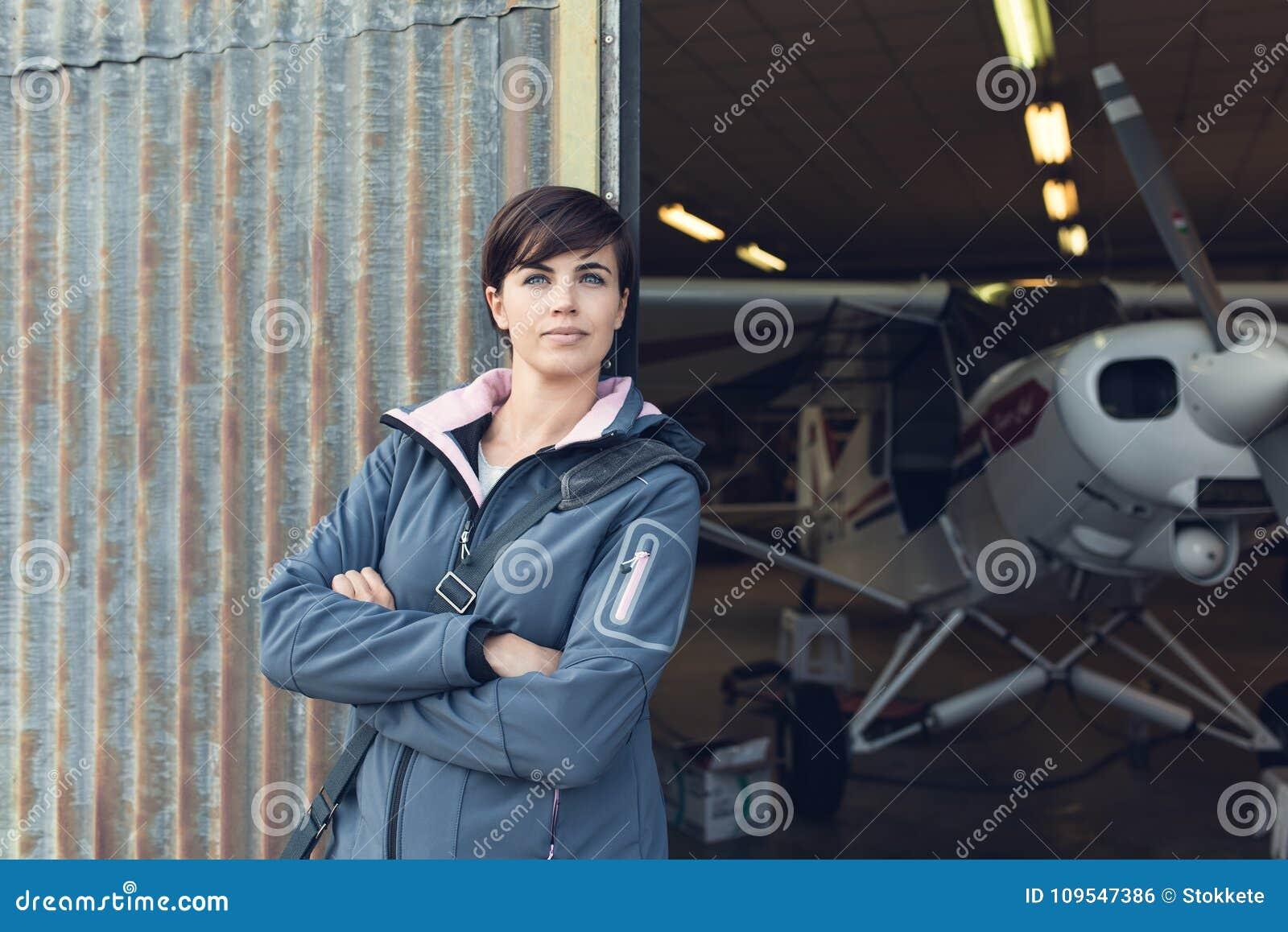 Uśmiechnięta kobieta opiera przeciw hangar ścianom