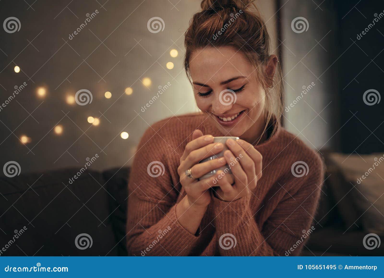 Uśmiechnięta kobieta pije kawę w zimie w domu