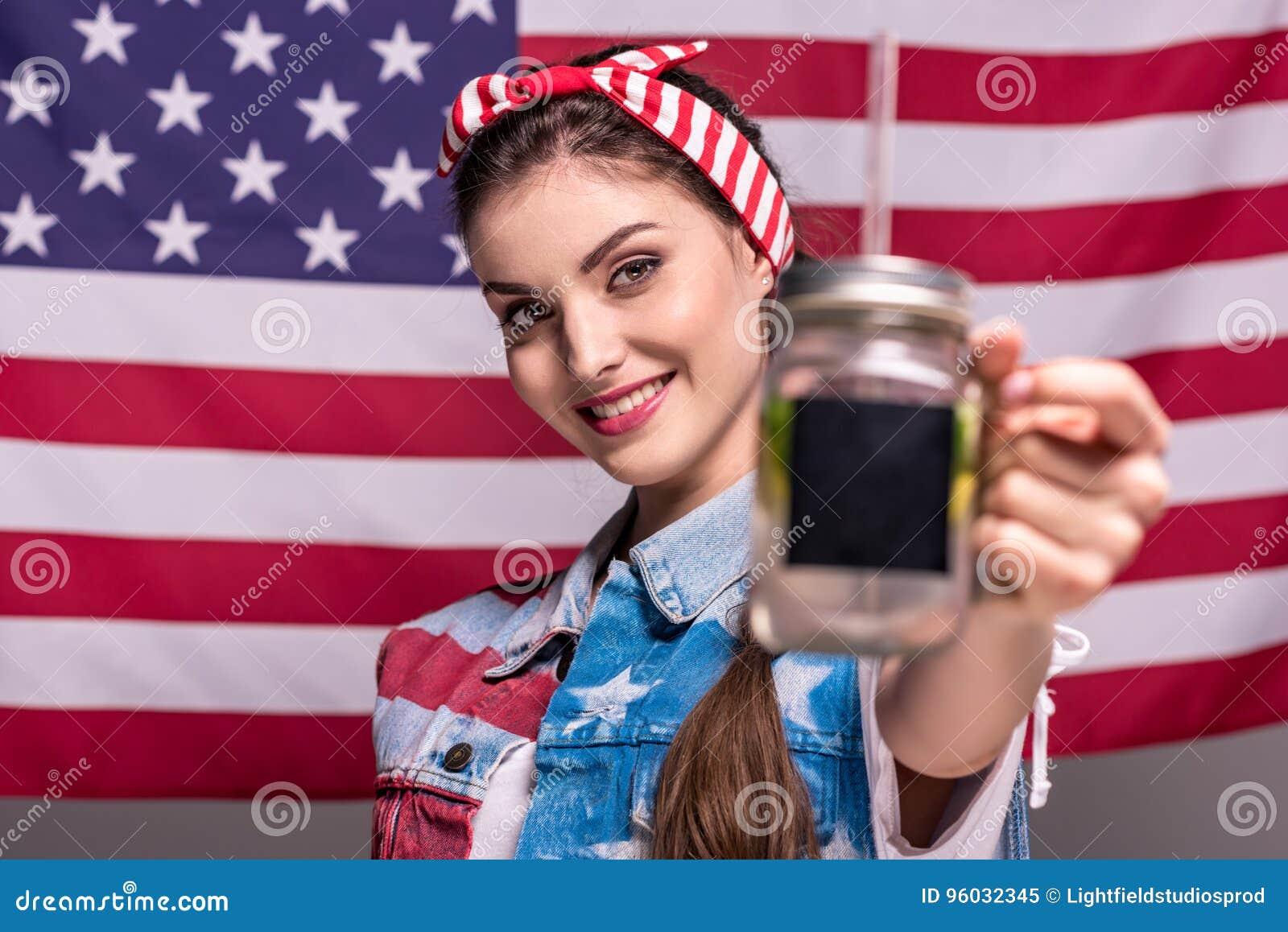 Uśmiechnięta kobieta pokazuje detox napój w ręce z flaga amerykańską na tle
