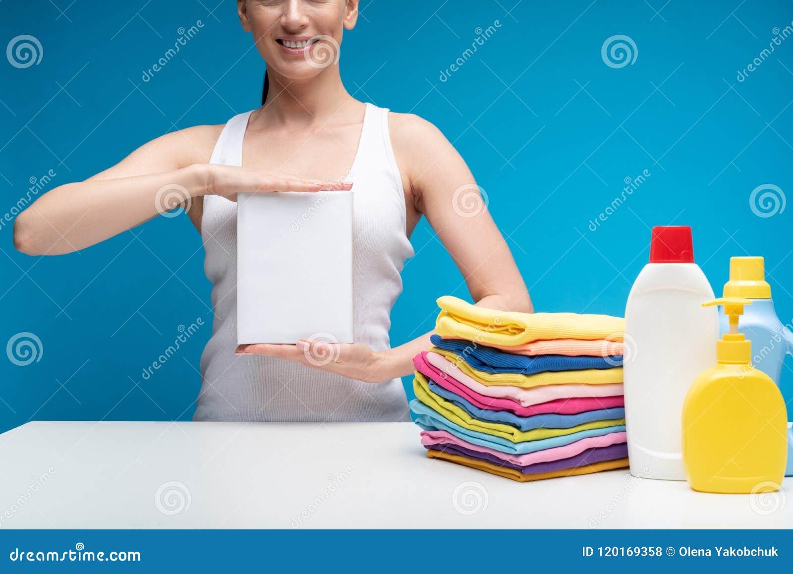 Uśmiechnięta kobieta pokazuje ona ulubionego detergent
