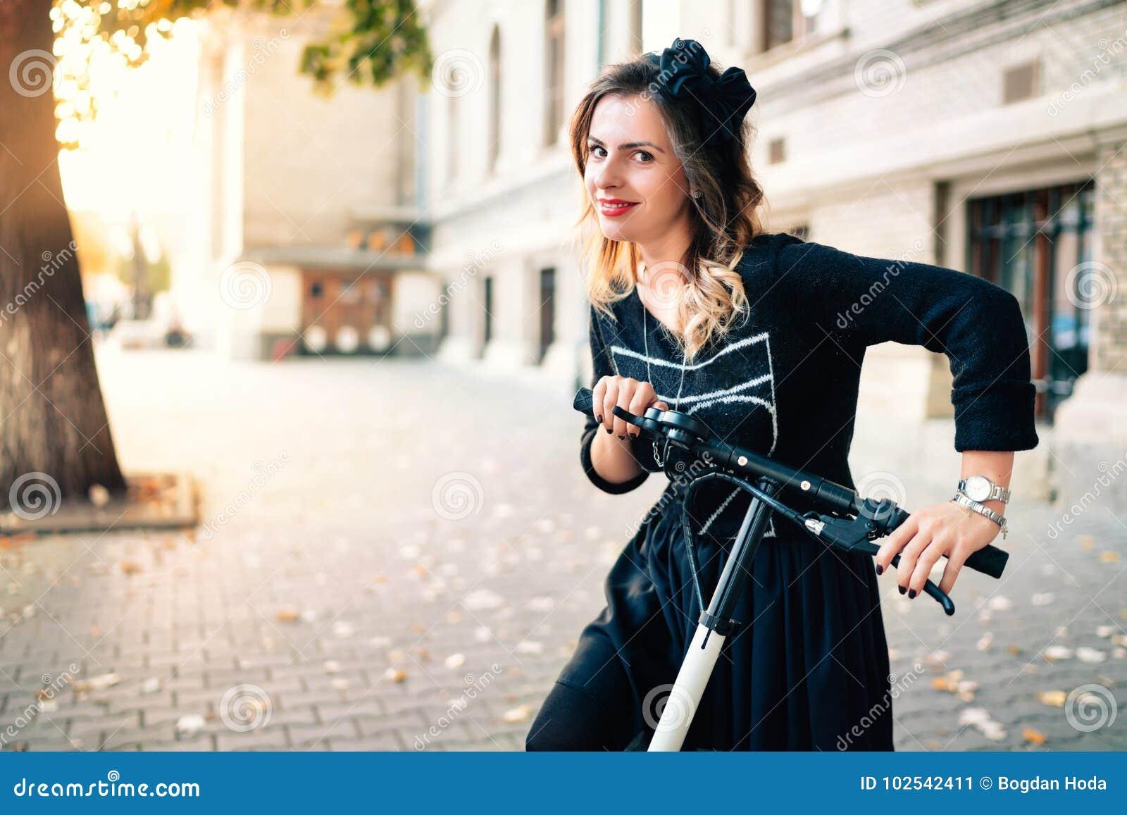 Uśmiechnięta kobieta z elektryczną kopnięcie hulajnoga na pięknym jesień dniu