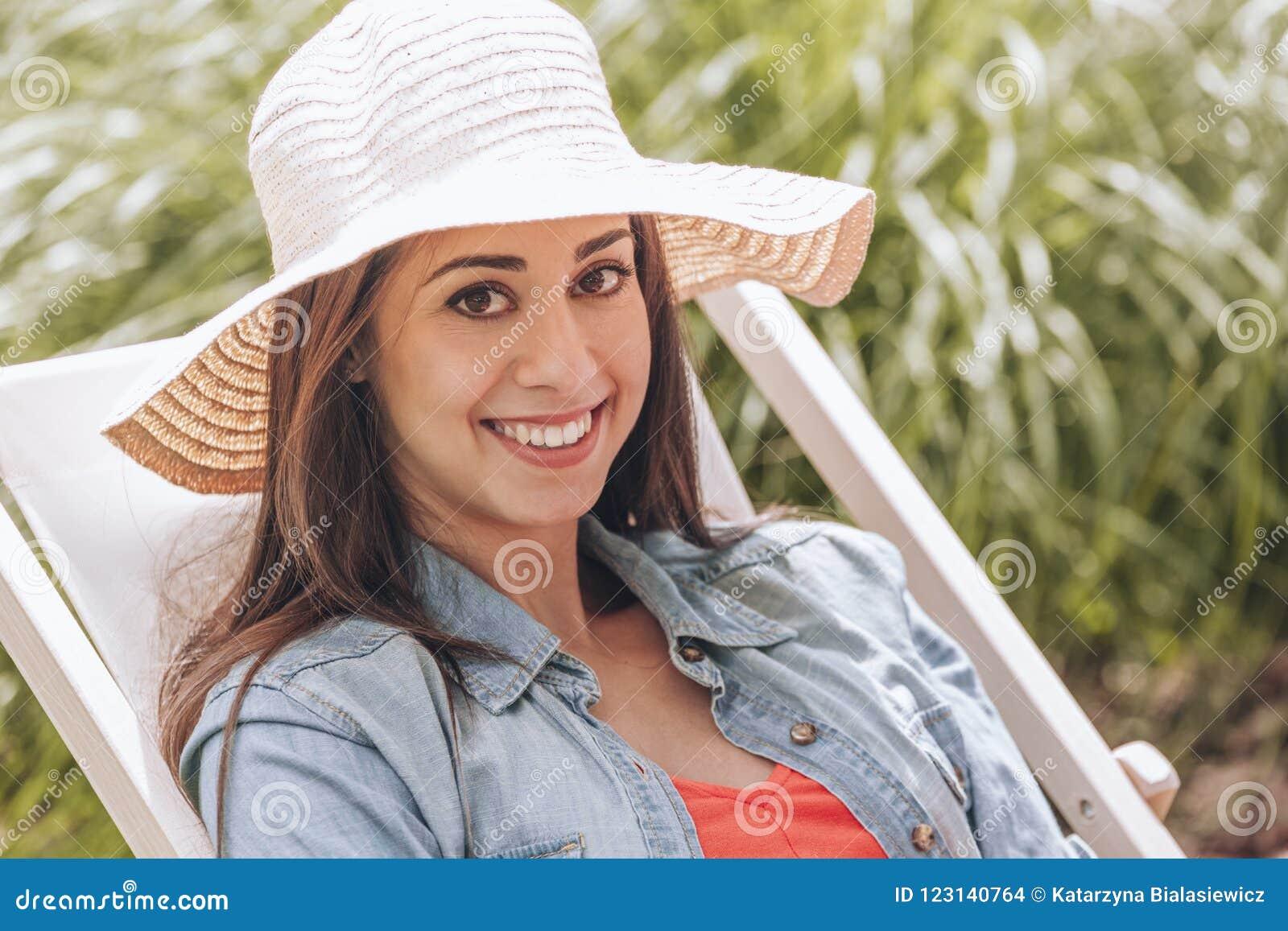 Uśmiechnięta kobieta z kapeluszowy relaksować dalej sunbed w lecie
