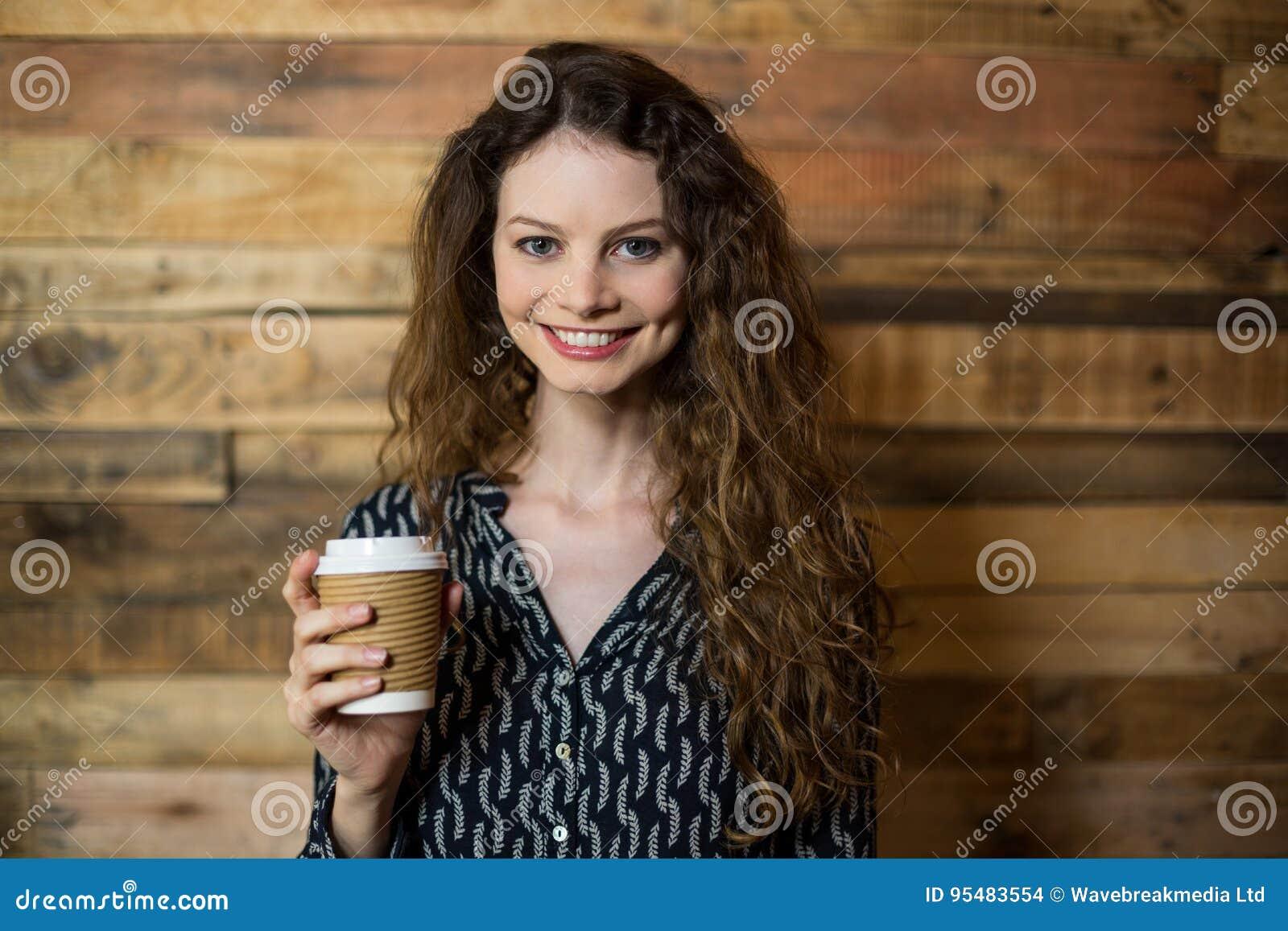 Uśmiechnięta kobiety pozycja z rozporządzalną filiżanką w café