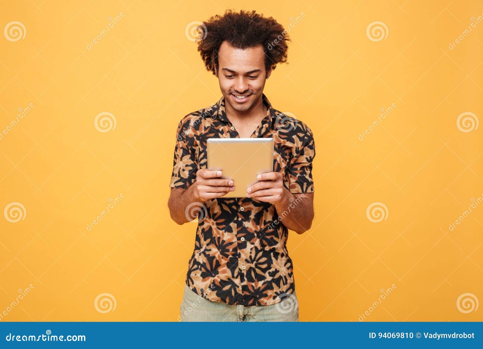 Uśmiechnięta młoda afro amerykańska facet pozycja i używać komputer osobisty pastylkę