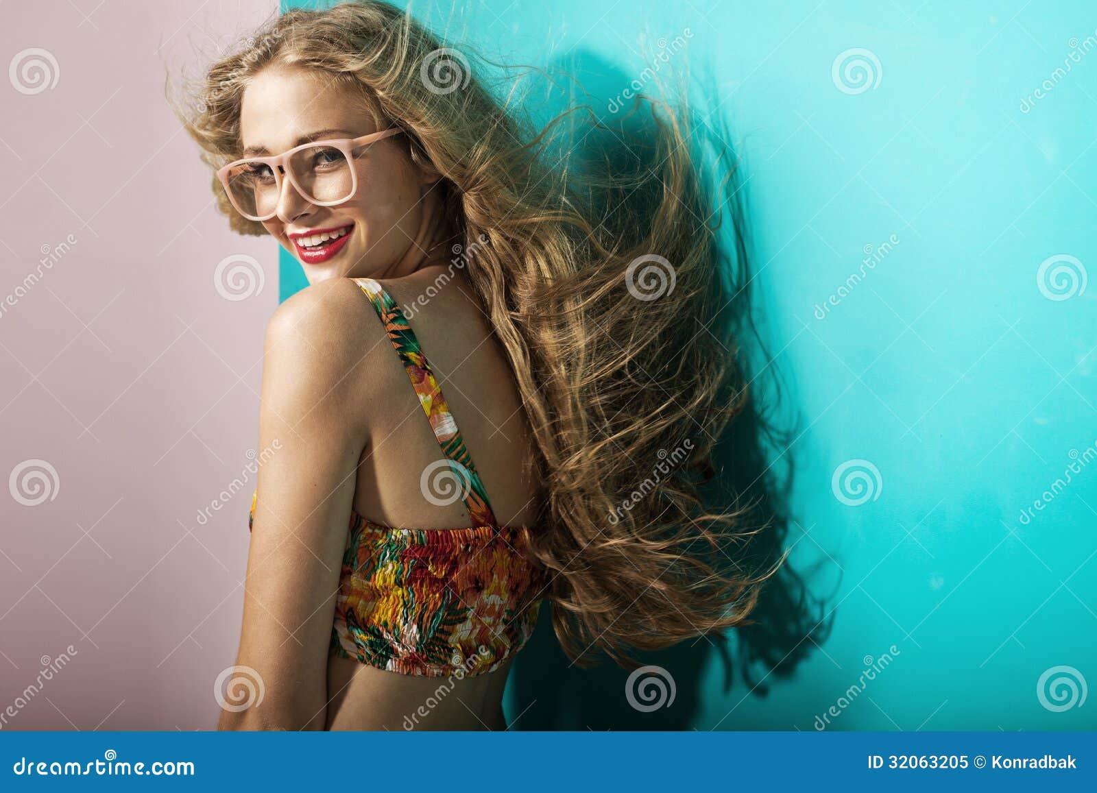 Uśmiechnięta młoda blondynki kobieta z jasną skórą