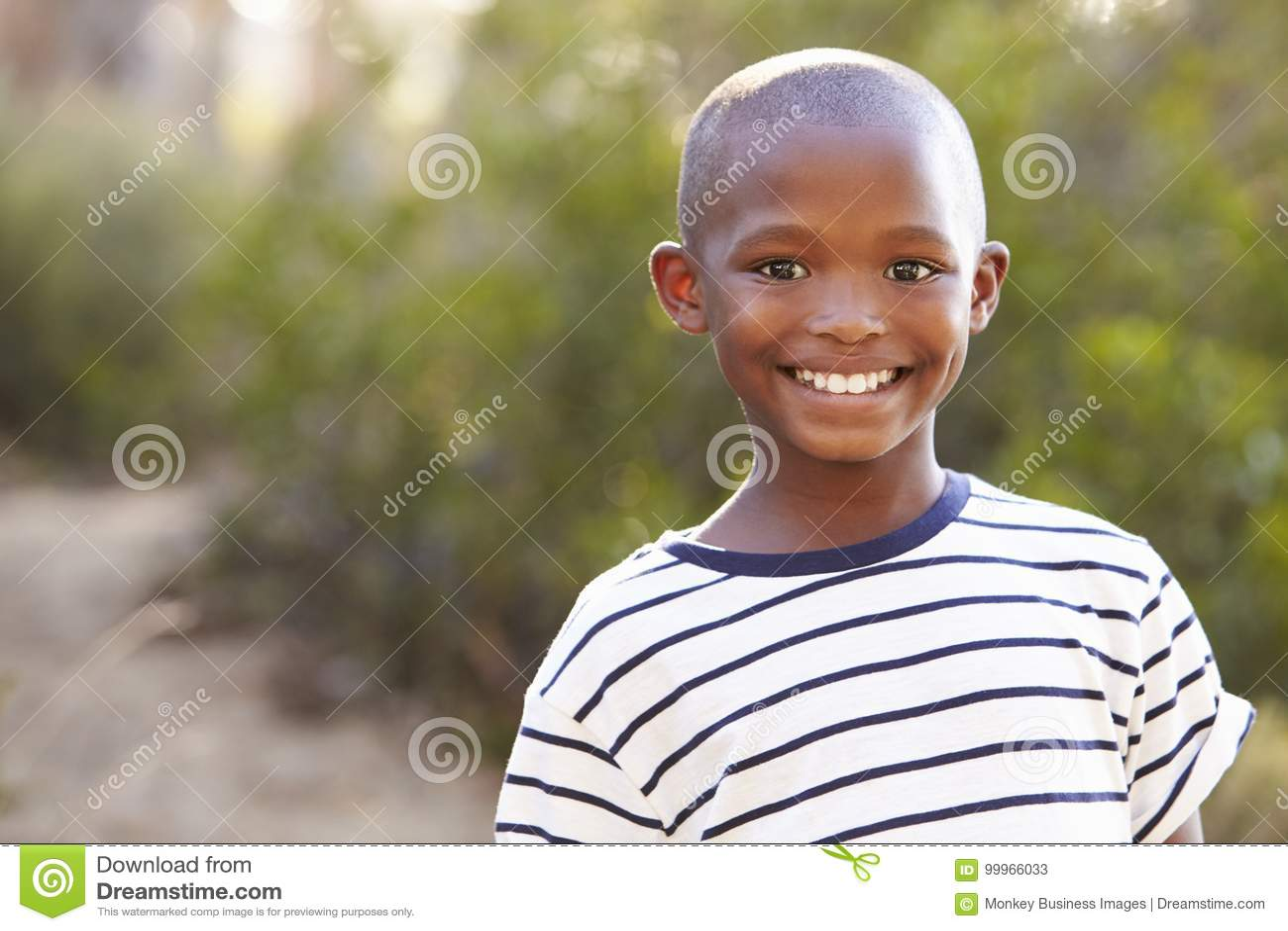Uśmiechnięta młoda czarna chłopiec patrzeje kamera outdoors