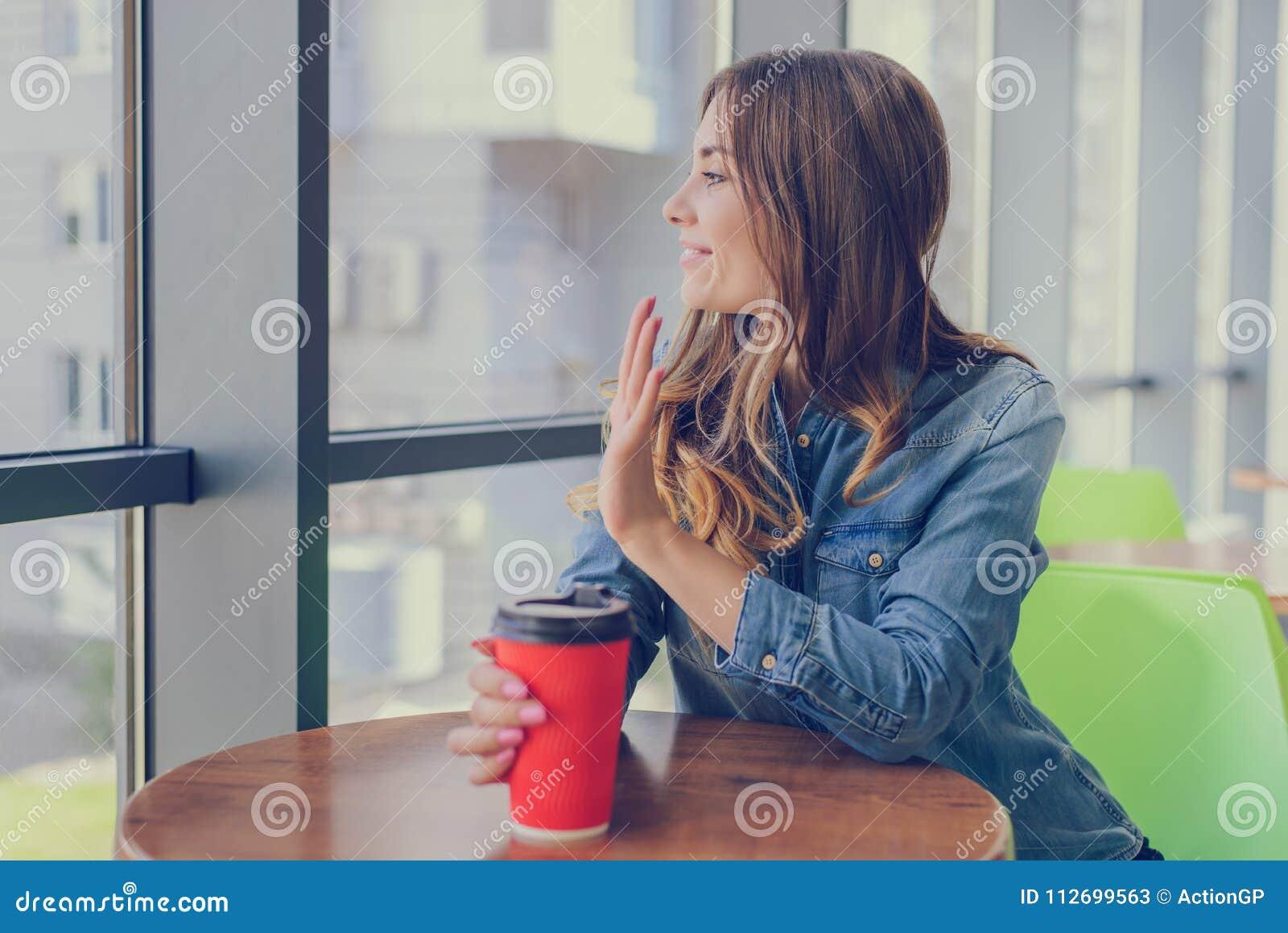 Uśmiechnięta młoda dziewczyna w cajg koszulowej pije kawie, siedzący w kawiarni i machający jej przyjaciel Takeaway sklep iść kaw