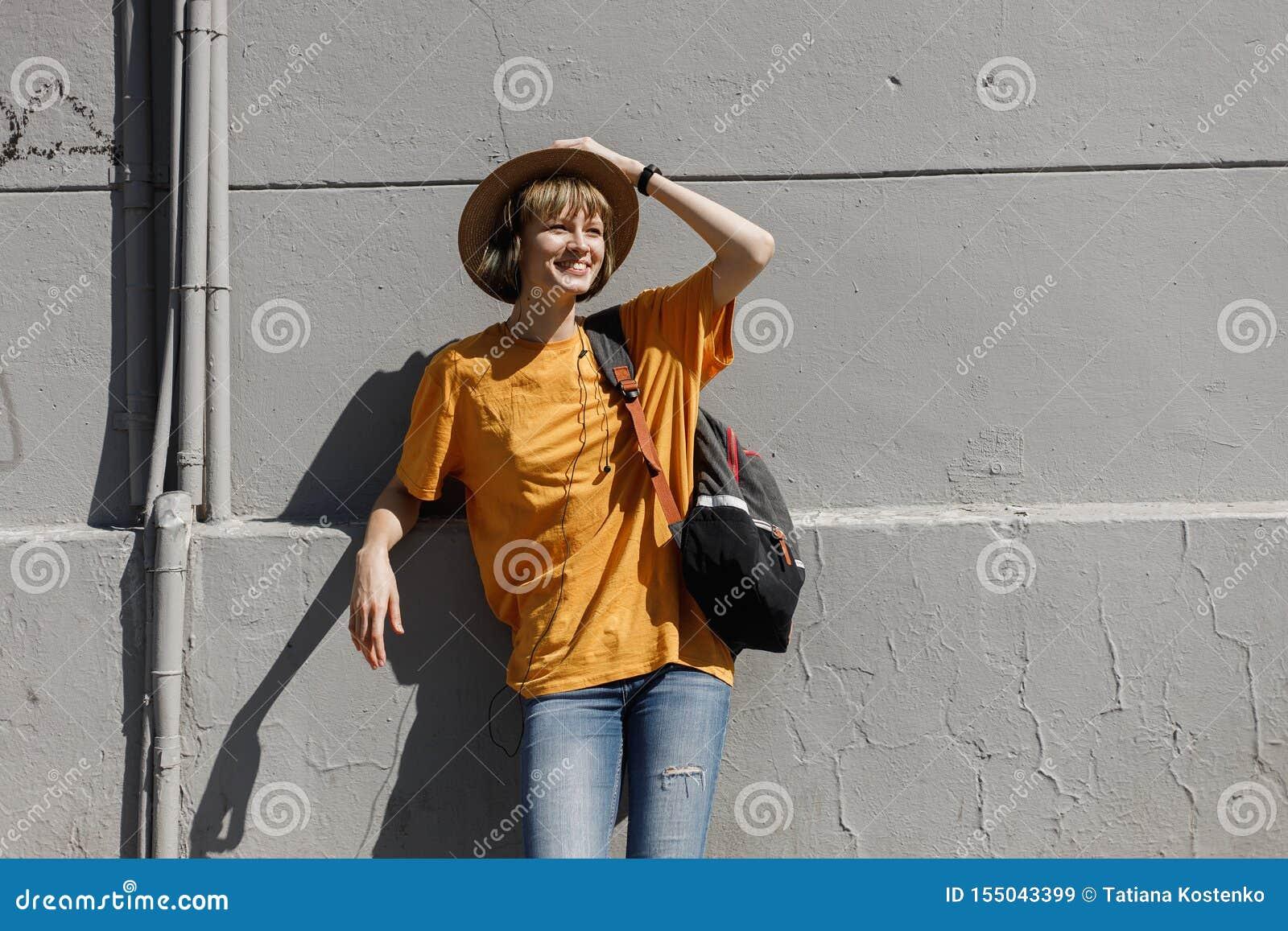 Uśmiechnięta młoda dziewczyna z plecakiem ubierał w żółtej koszulce i słomiany kapelusz stoi opierać na szarym budynku w mieście