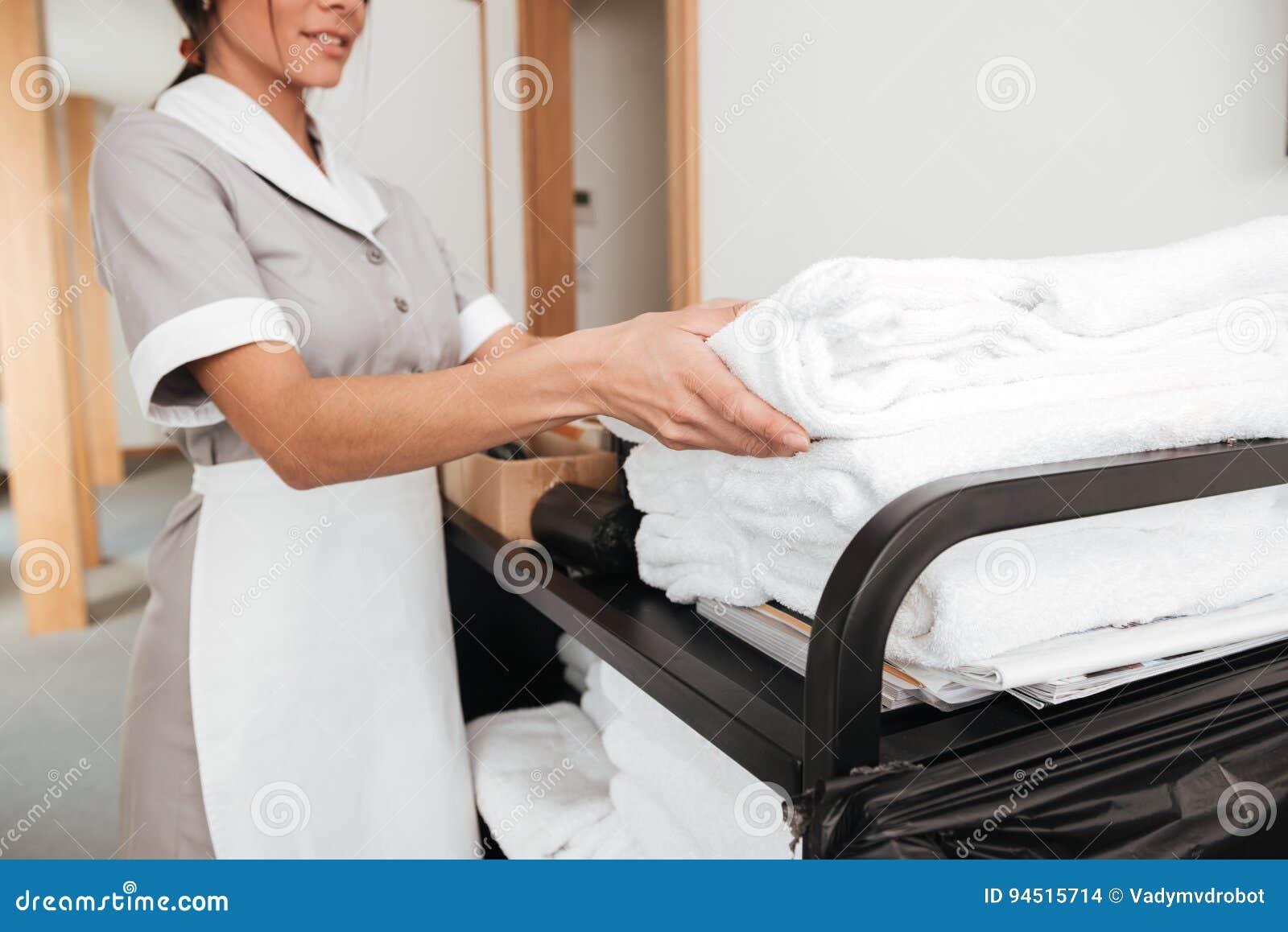 Uśmiechnięta młoda gosposia bierze świeżych ręczniki od housekeeping fury