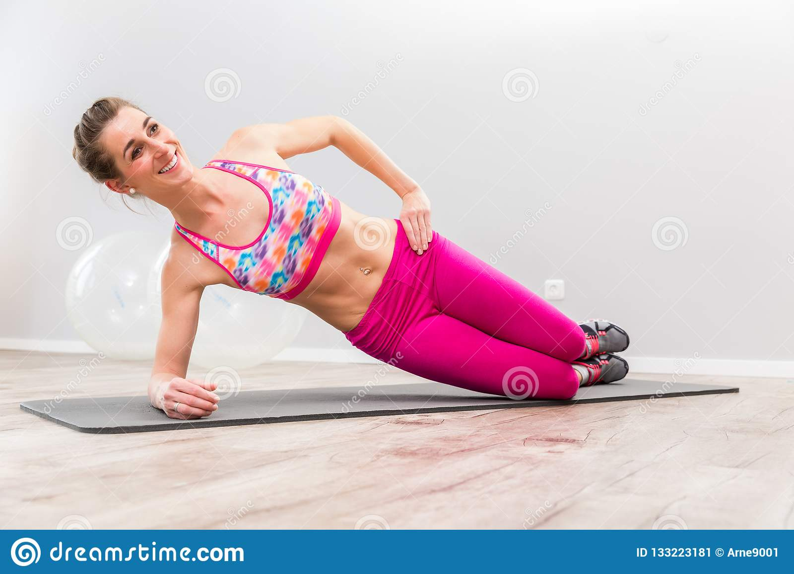 Uśmiechnięta młoda kobieta ćwiczy na macie