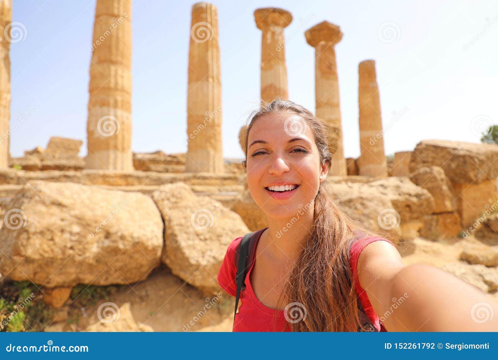Uśmiechnięta młoda kobieta bierze jaźń portret z grecką świątynią na tle w dolinie świątynie przy Agrigento, Włochy