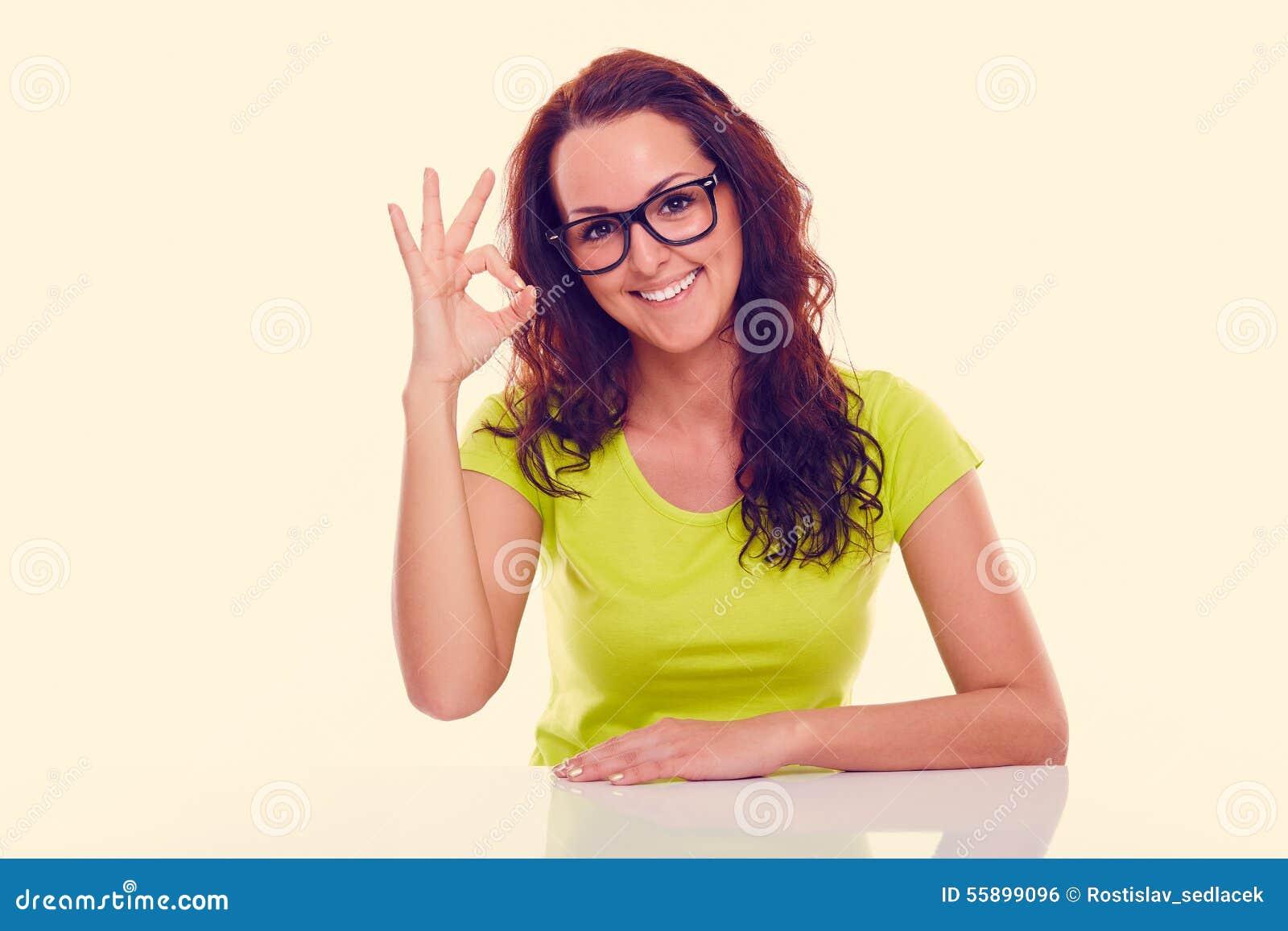 Uśmiechnięta młoda kobieta gestykuluje ok stonowany