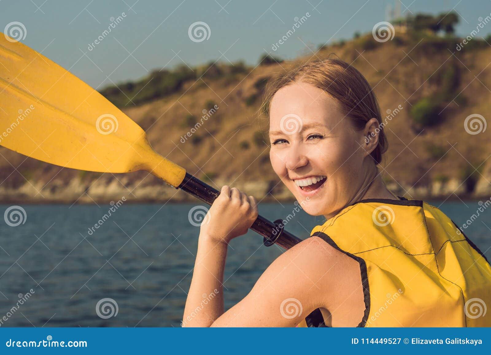 Uśmiechnięta młoda kobieta kayaking na morzu Szczęśliwy młodej kobiety kajakarstwo w morzu na letnim dniu