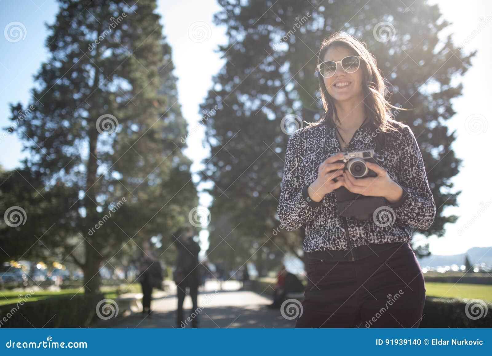 Uśmiechnięta młoda kobieta opowiada na jej smartphone na ulicie Komunikujący z przyjaciółmi, uwalnia wezwania i wiadomości dla mł