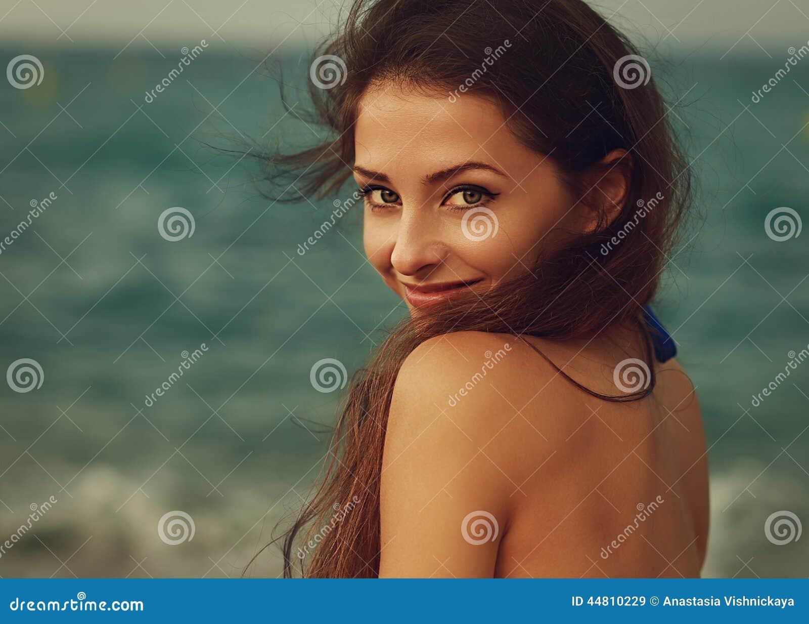 Uśmiechnięta młoda kobieta patrzeje szczęśliwy na morzu
