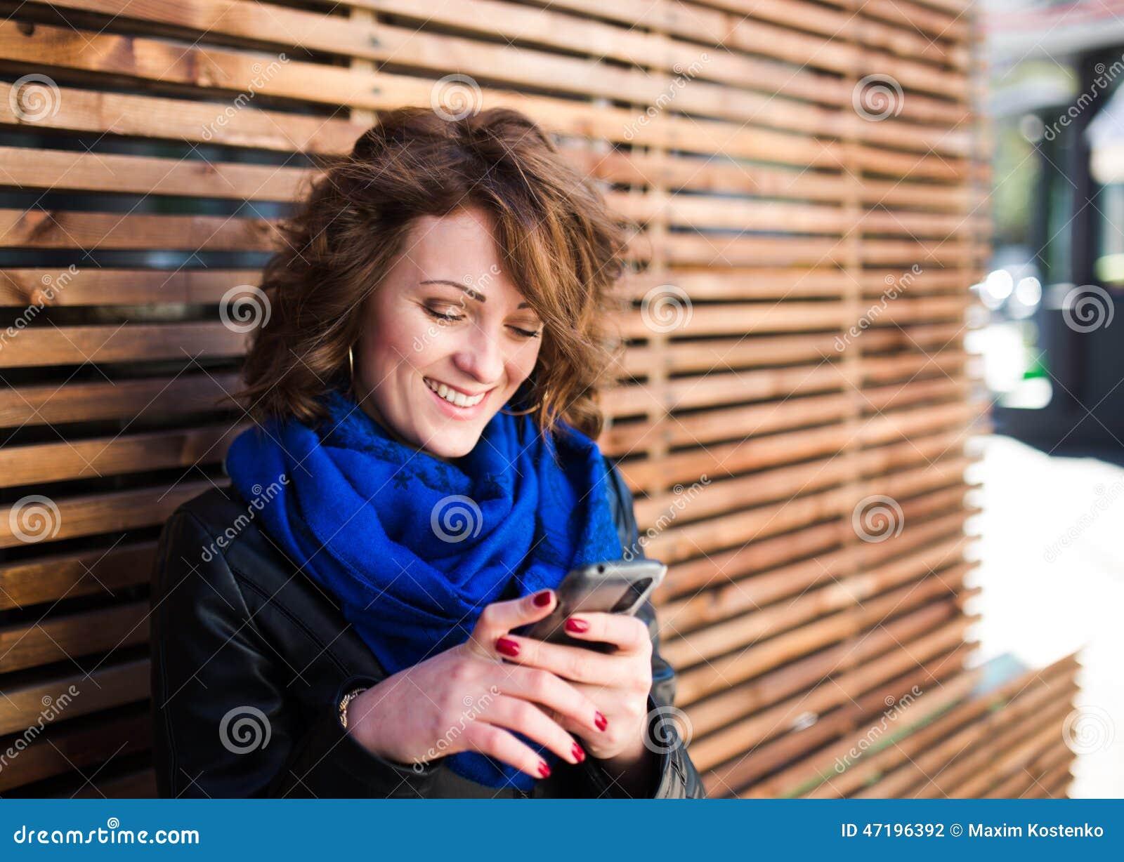 Uśmiechnięta młoda kobieta używa smartphone na ulicie