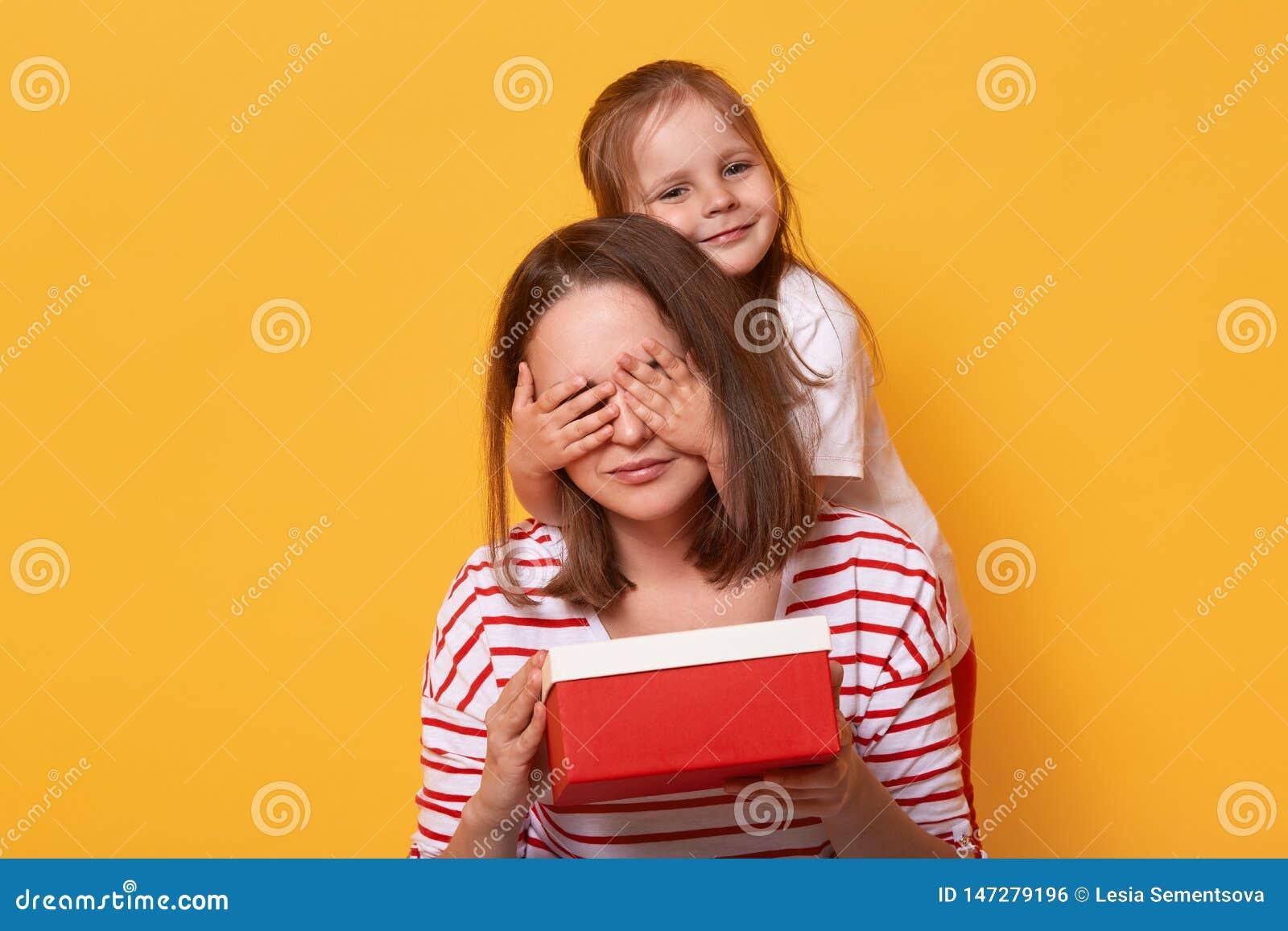 Uśmiechnięta mała córka zamyka oczy jej mama i daje ona czerwieni pudełku, teraźniejszość dla matka dnia, niespodzianka dla mamus