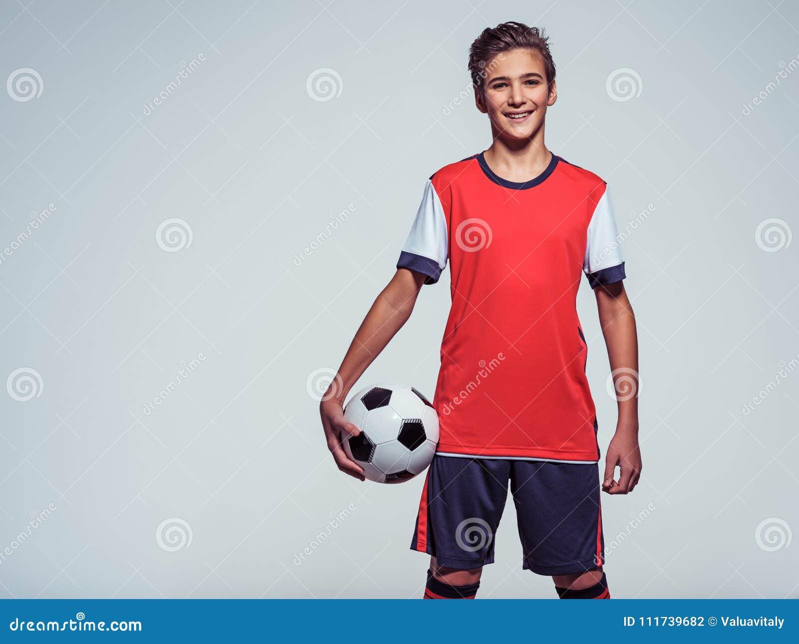 Uśmiechnięta nastoletnia chłopiec w sportswear mienia piłki nożnej piłce