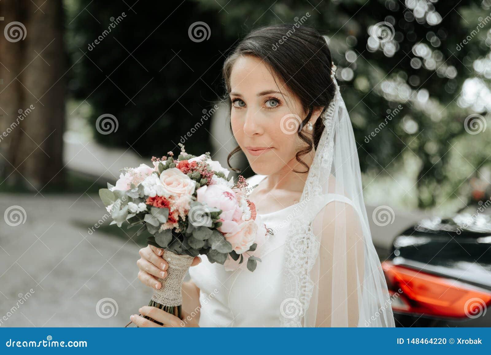 Uśmiechnięta panna młoda trzyma bridal bukiet w ślubnej sukni i przesłona