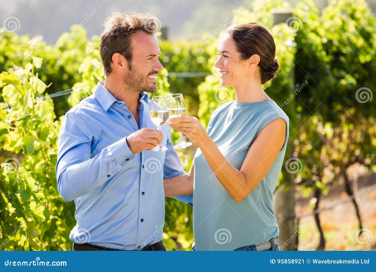 Uśmiechnięta para wznosi toast wineglasses przy winnicą