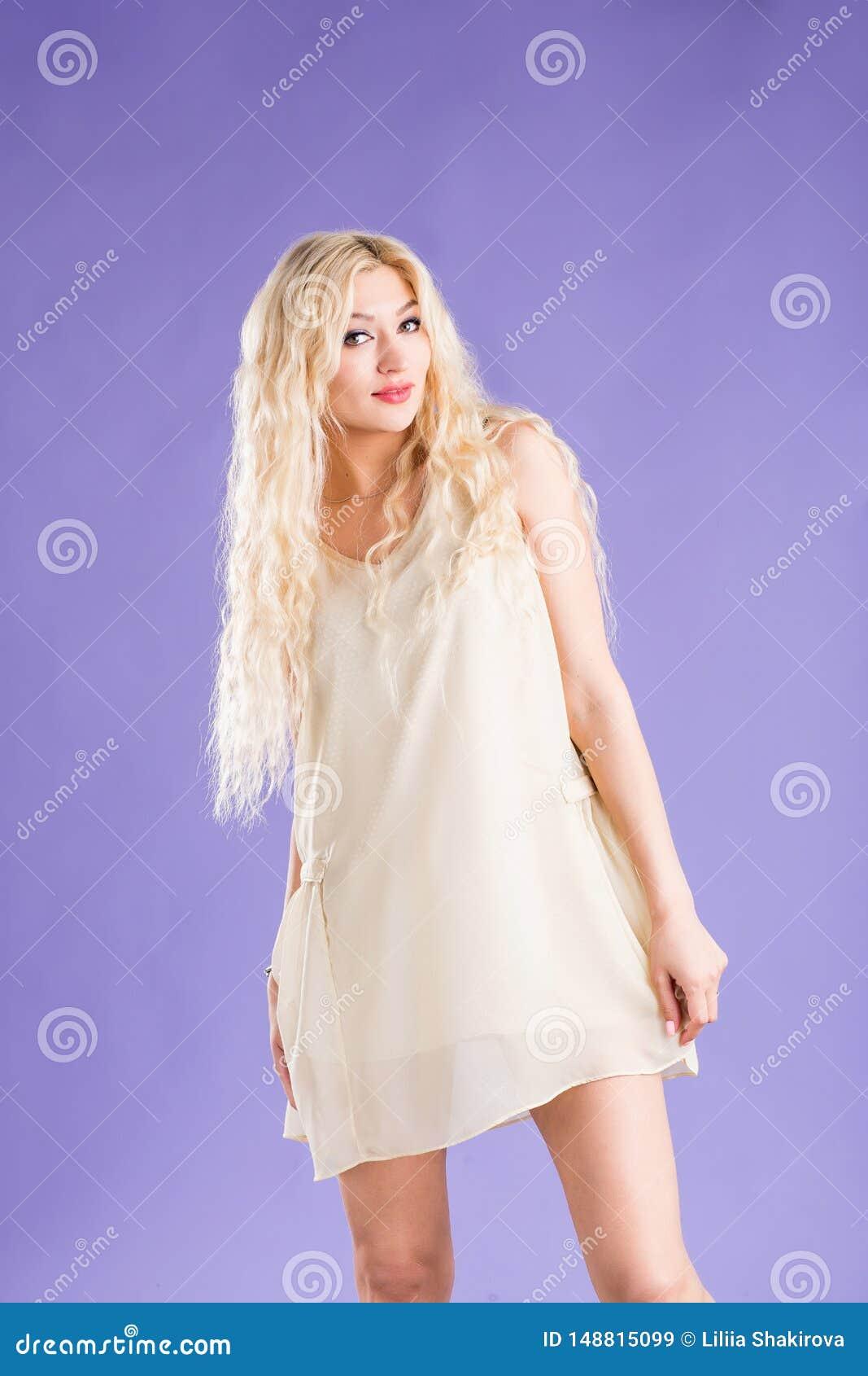 Uśmiechnięta piękna blondynki kobieta na fiołkowym tle