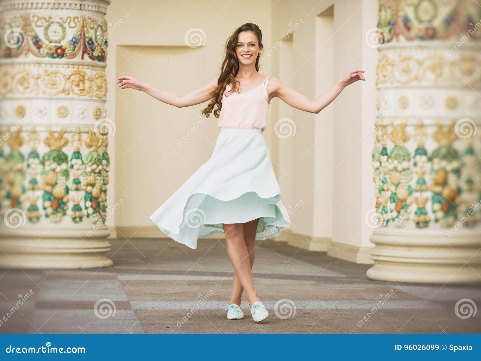 Uśmiechnięta piękna młoda kobieta pozuje outdoors