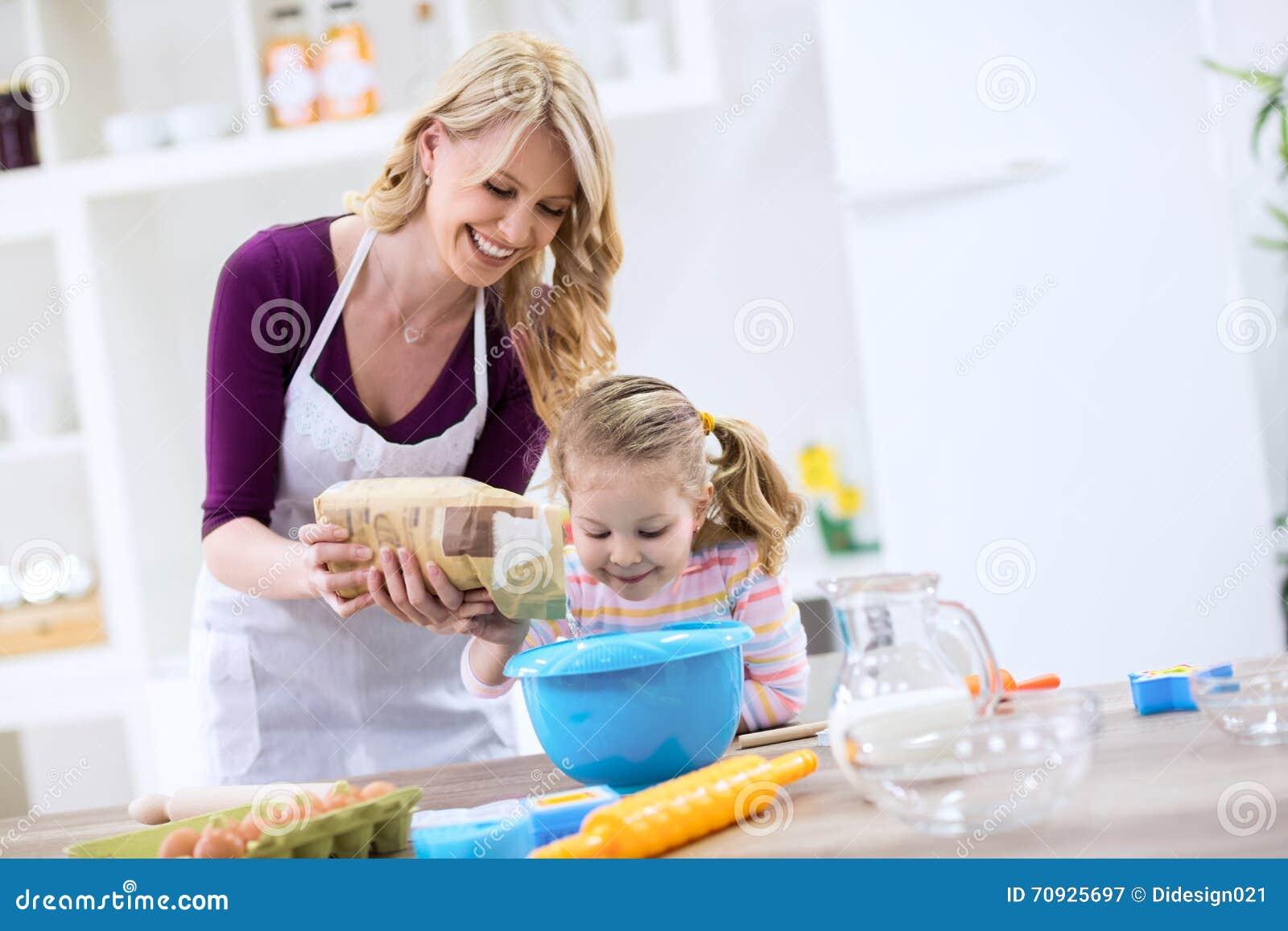 Uśmiechnięta piękna mama z dziecka kładzenia mąką