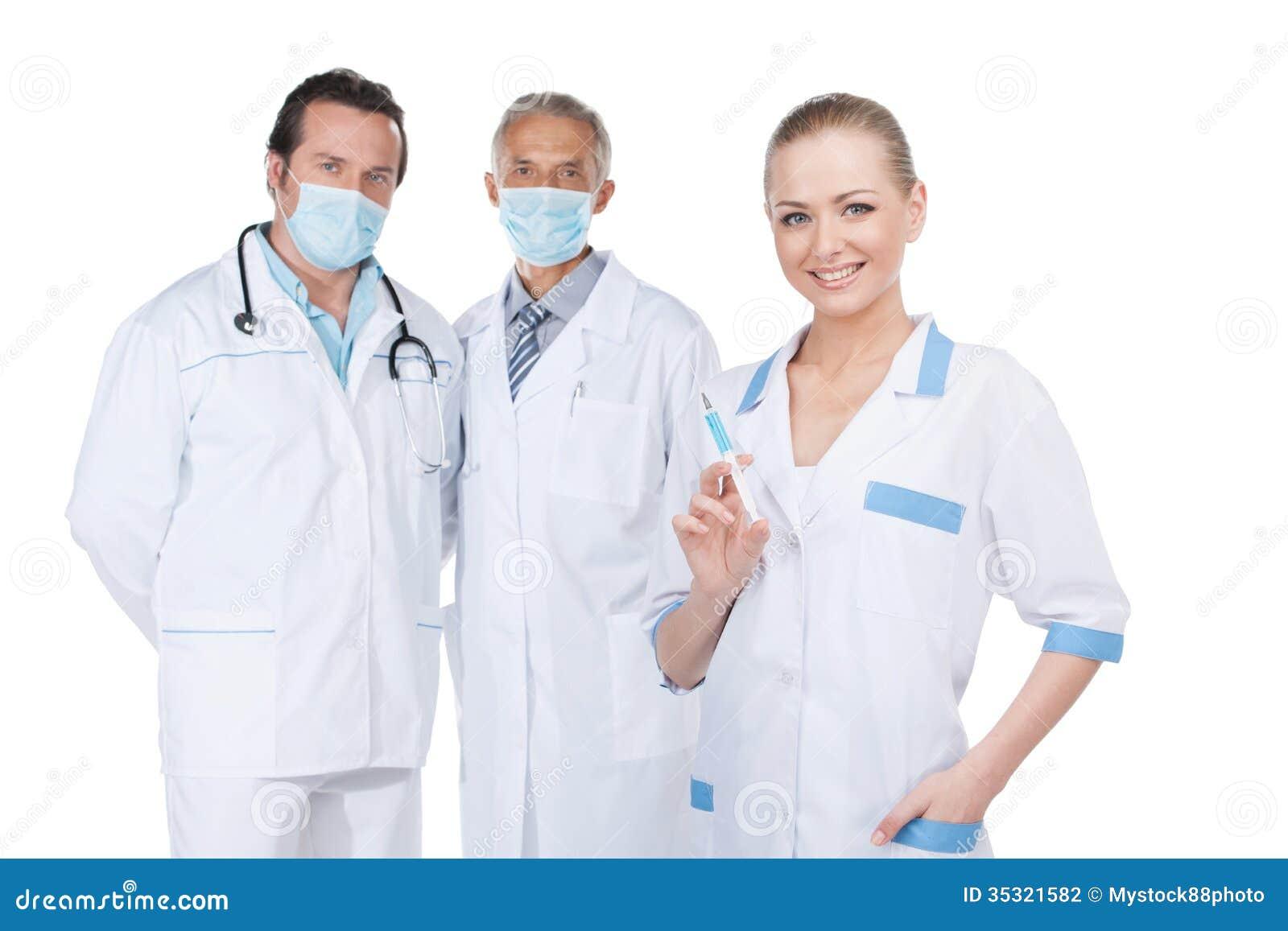 Uśmiechnięta piękna pielęgniarka na przedpolu z strzykawką.