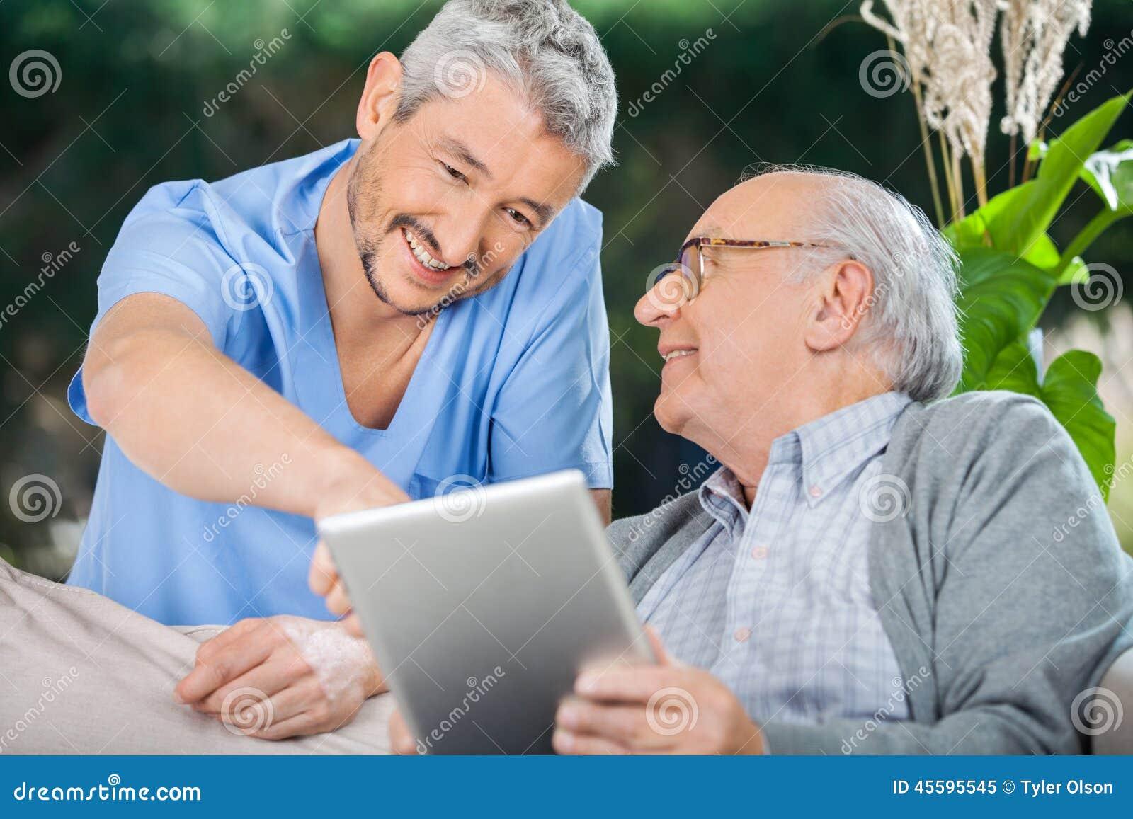 Uśmiechnięta pielęgniarka Pomaga Starszego mężczyzna Używa W pastylce