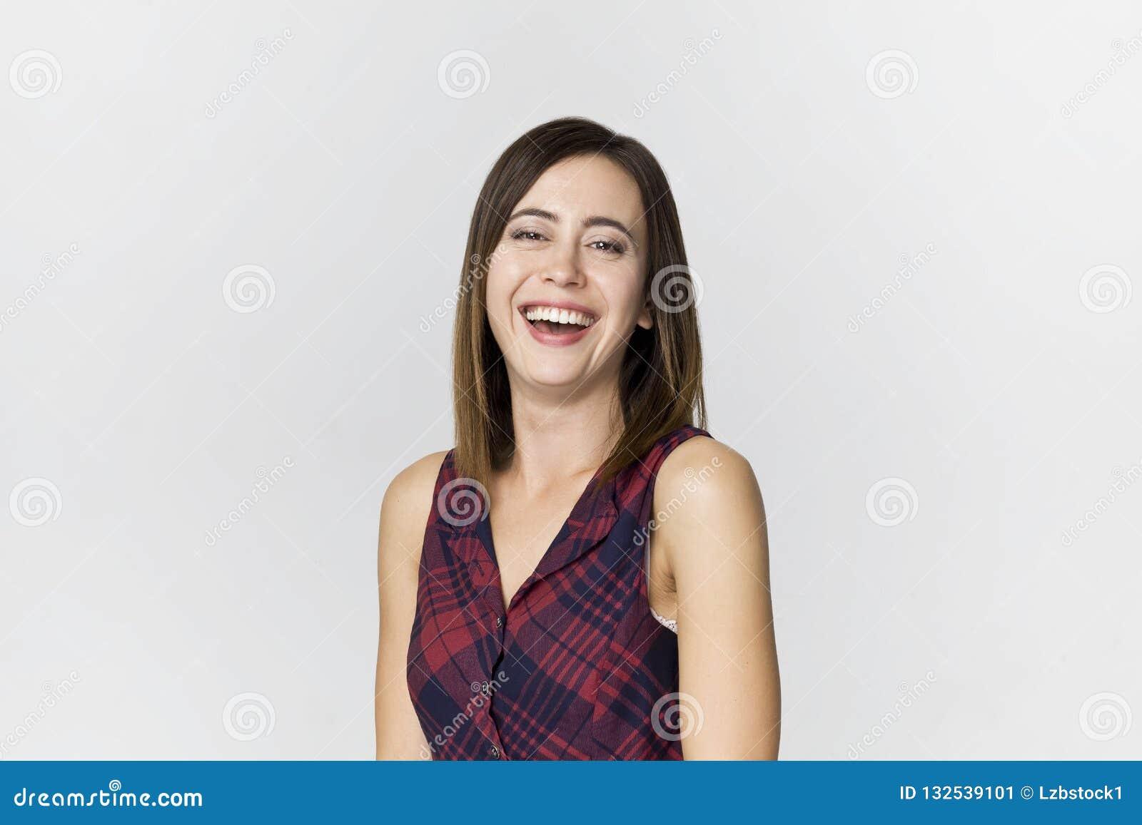 Uśmiechnięta pozytywna kobieta z atrakcyjnym spojrzeniem, będący ubranym kolorową suknię, pozuje przeciw białej pustej ścianie