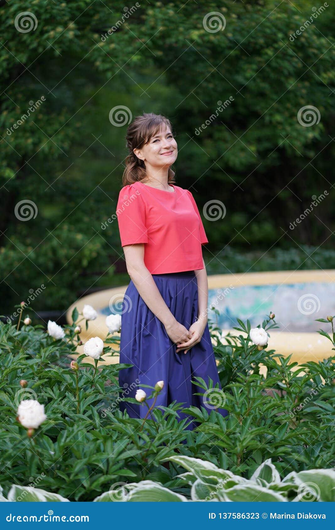 Uśmiechnięta szczęśliwa caucasian dorosła kobieta relaksuje w jej ogródzie z kwitnieniem kwitnie