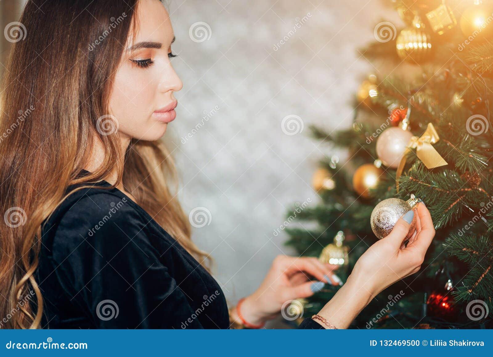Uśmiechnięta szczęśliwa dziewczyna dekoruje choinki w studiu Kobieta jest ubranym ładną czerni suknię, zakończenie w górę