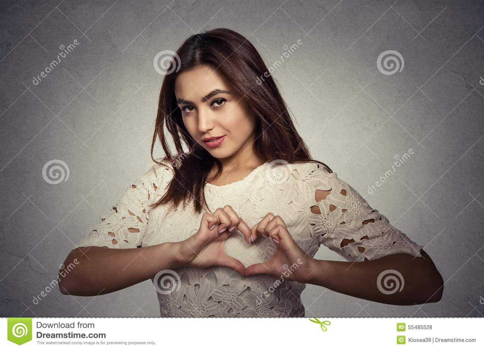 Uśmiechnięta szczęśliwa młoda kobieta robi sercu podpisywać z rękami
