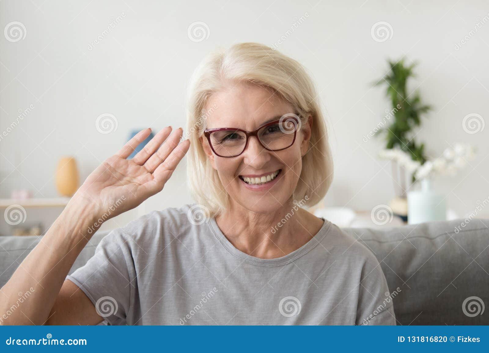 Uśmiechnięta w średnim wieku kobiety falowania ręka patrzeje kamerę, portrai