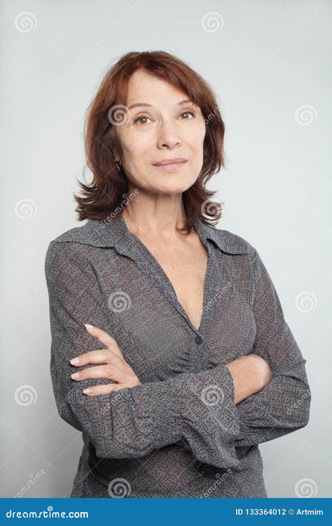 Uśmiechnięta w połowie dorosła biznesowa kobieta z krzyżować rękami na bielu