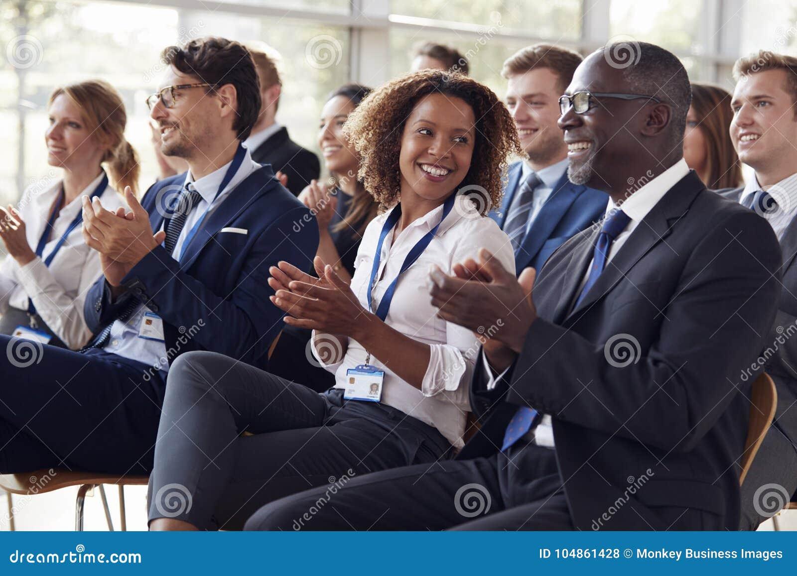 Uśmiechnięta widownia oklaskuje przy biznesowym konwersatorium