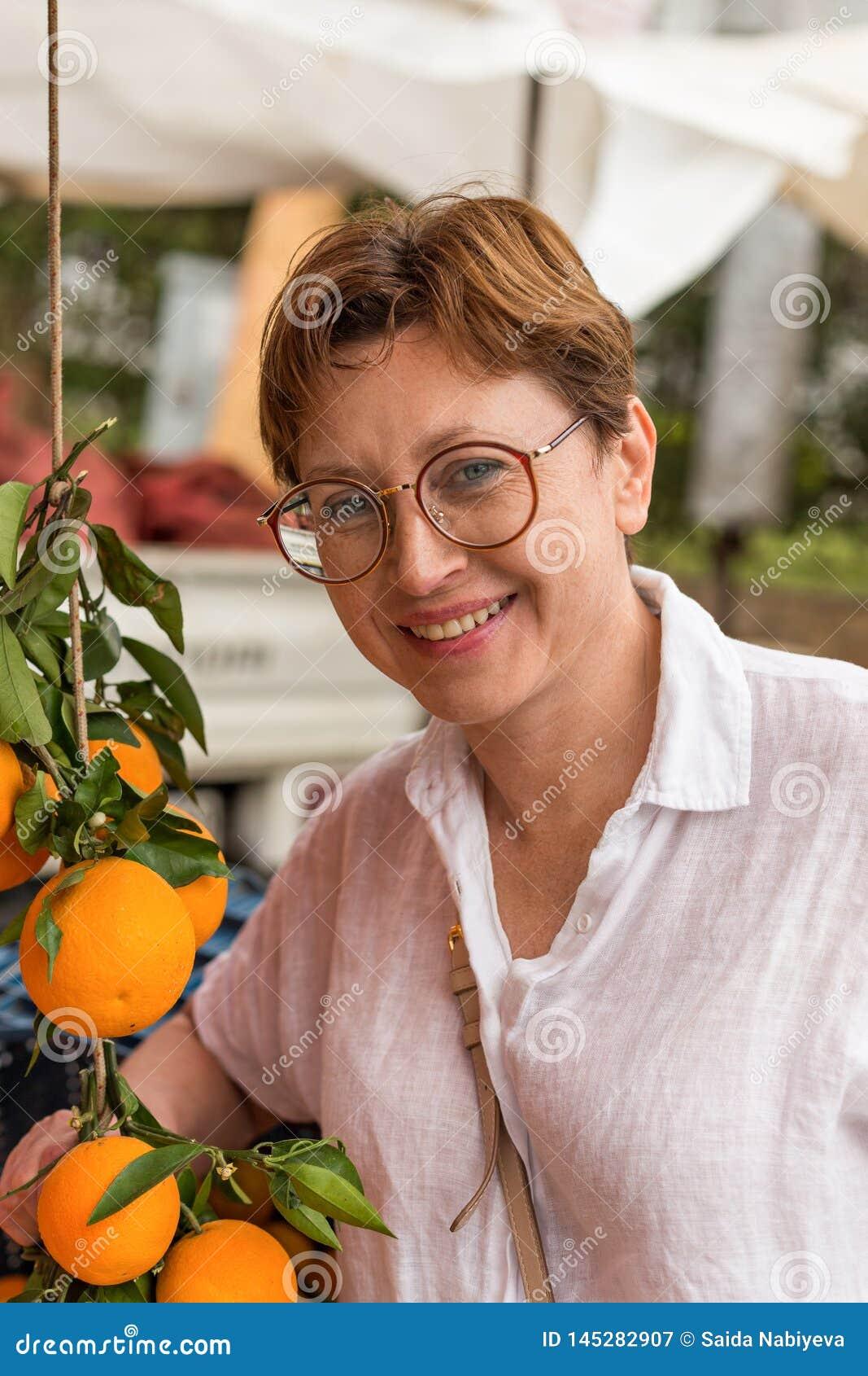 Uśmiechnięta wiek średni kobieta przy sklepu spożywczego rynkiem